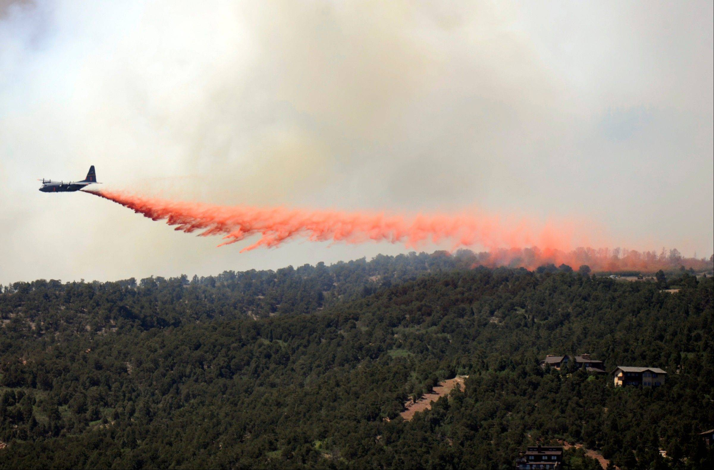 A C-130 makes a drop on the Waldo Canyon wildfire in Colorado Springs, Colo., Tuesday, June 26, 2012. Colorado has endured nearly a week of 100-plus-degree days and low humidity, sapping moisture from timber and grass, creating a devastating formula for volatile wildfires across the state and punishing conditions for firefighters.