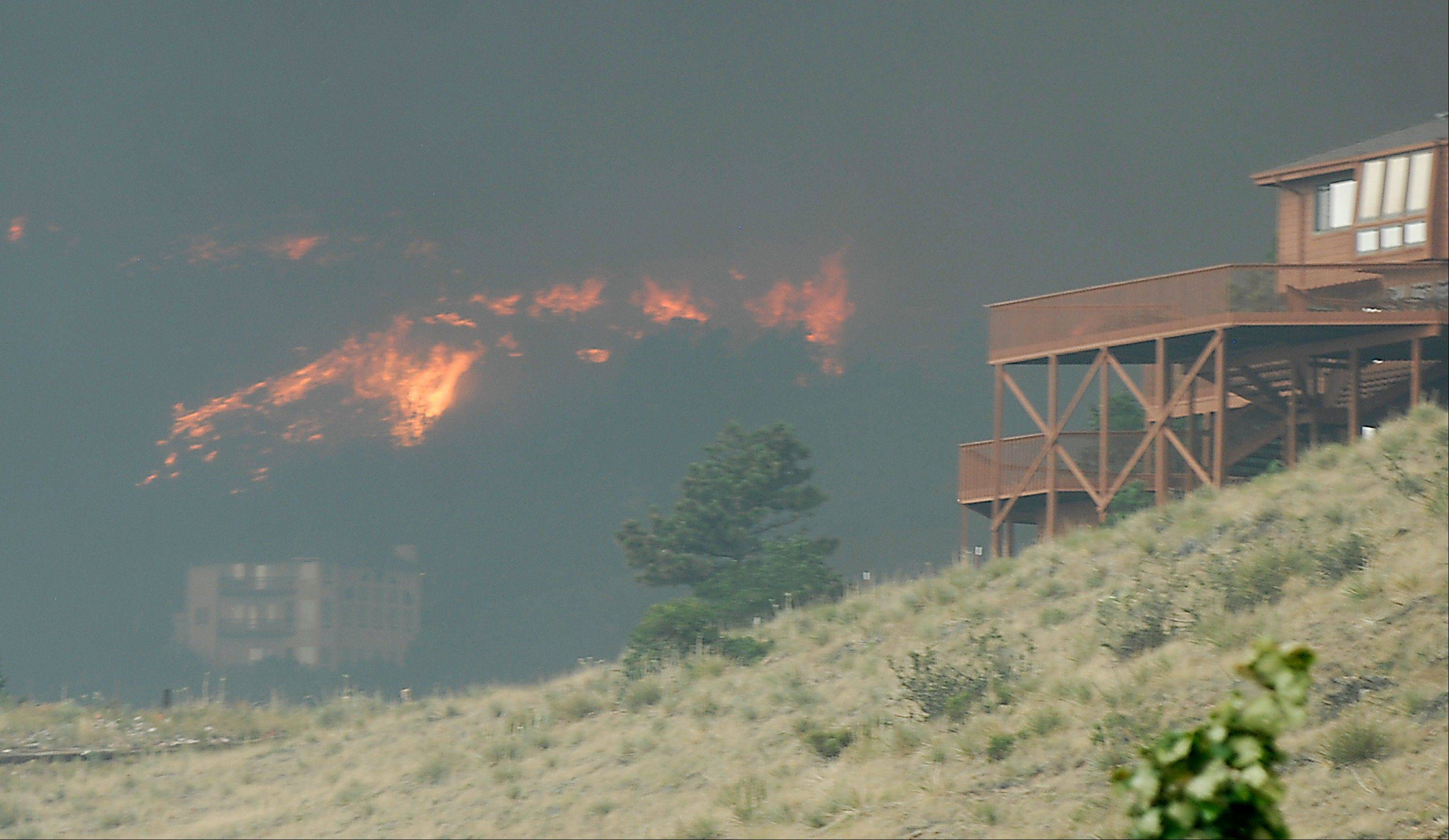 Flames and smoke from the Waldo Canyon Fire surround a home as it races down into western portions of Colorado Springs, Colo. on Tuesday, June 26, 2012 leaving a trail of destruction and burning homes and buildings in it's path. Heavily populated areas in the fire's path have been affected.