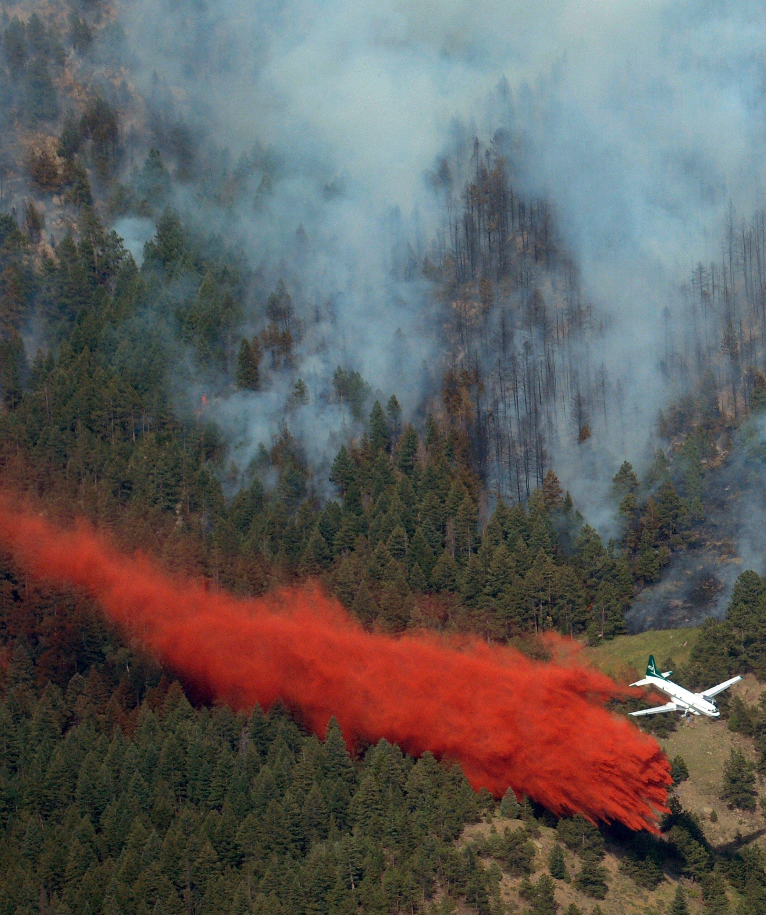 A slurry bomber tries to create a barrier to keep the fire from spreading near, Tuesday, June 26, 2012 near Boulder, Colo.