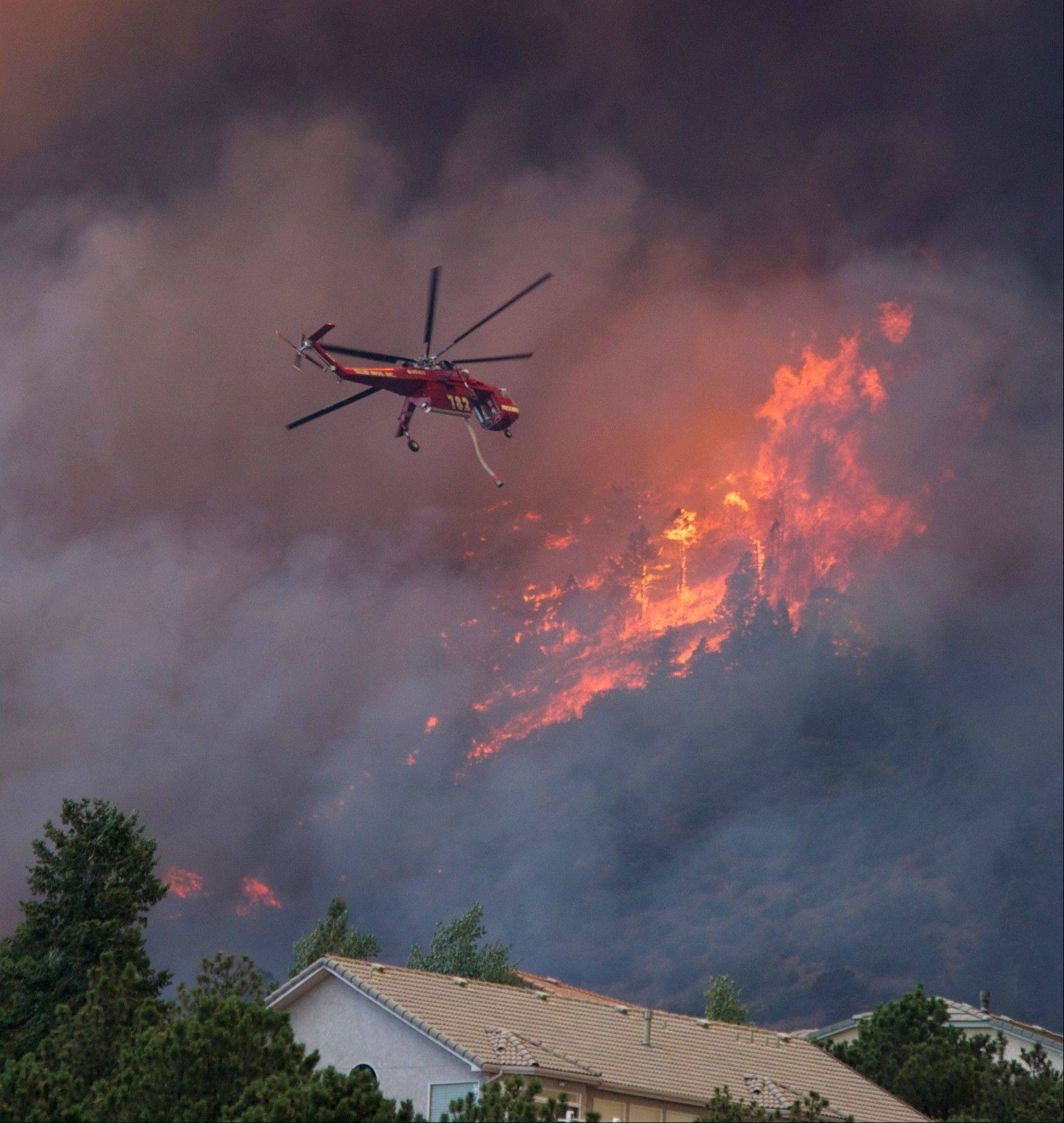 A helicopter tries to put out fire on the Waldo Canyon wildfire as it moved into subdivisions and destroyed homes in Colorado Springs, Colo., on Tuesday, June 26, 2012.