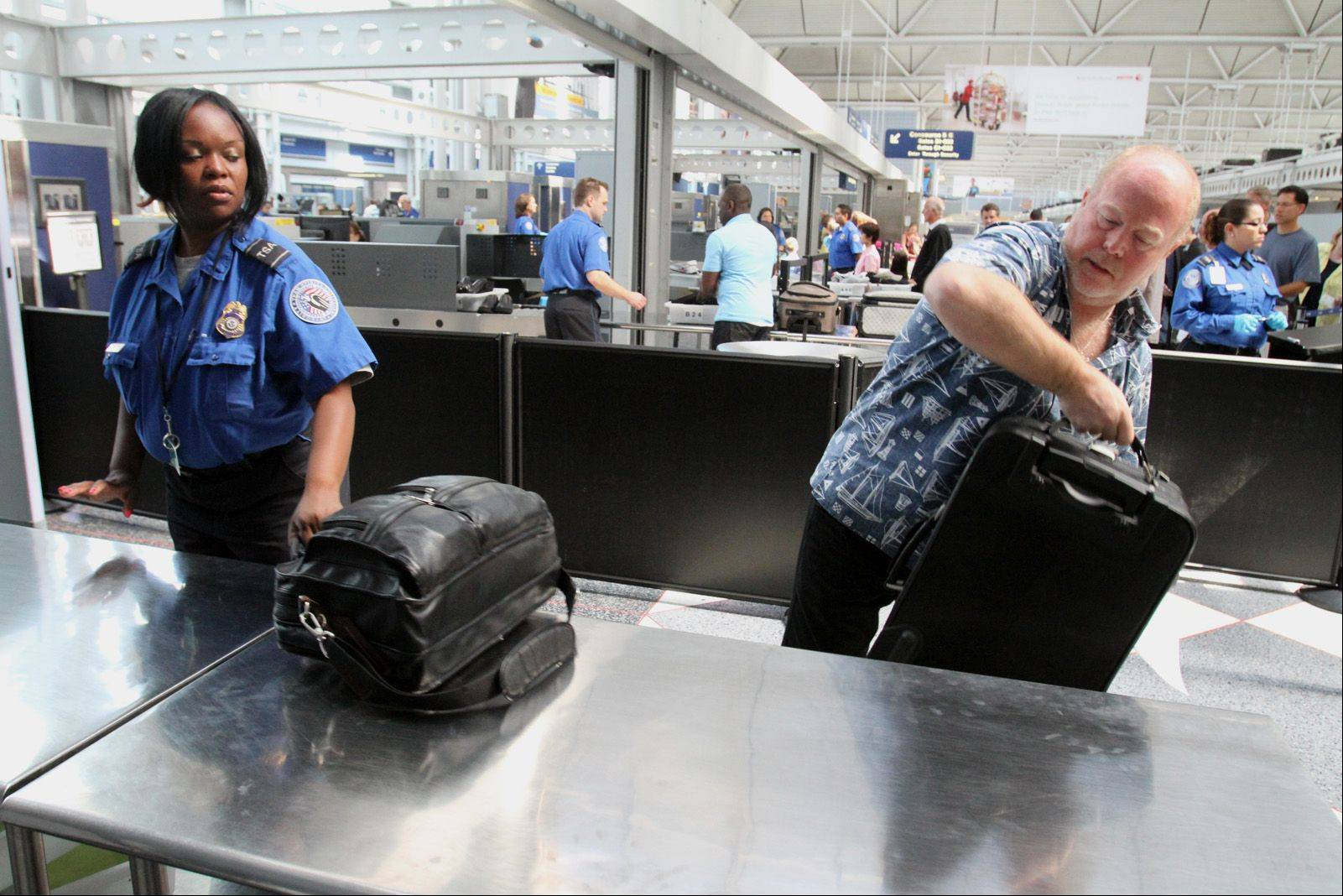 Laurent Perkin of San Diego, with his shoes on, goes through a new streamlined security checkpoint for preapproved travelers at the United Terminal at O'Hare International Airport in Chicago on Wednesday. Perkin was traveling home after business in Chicago.