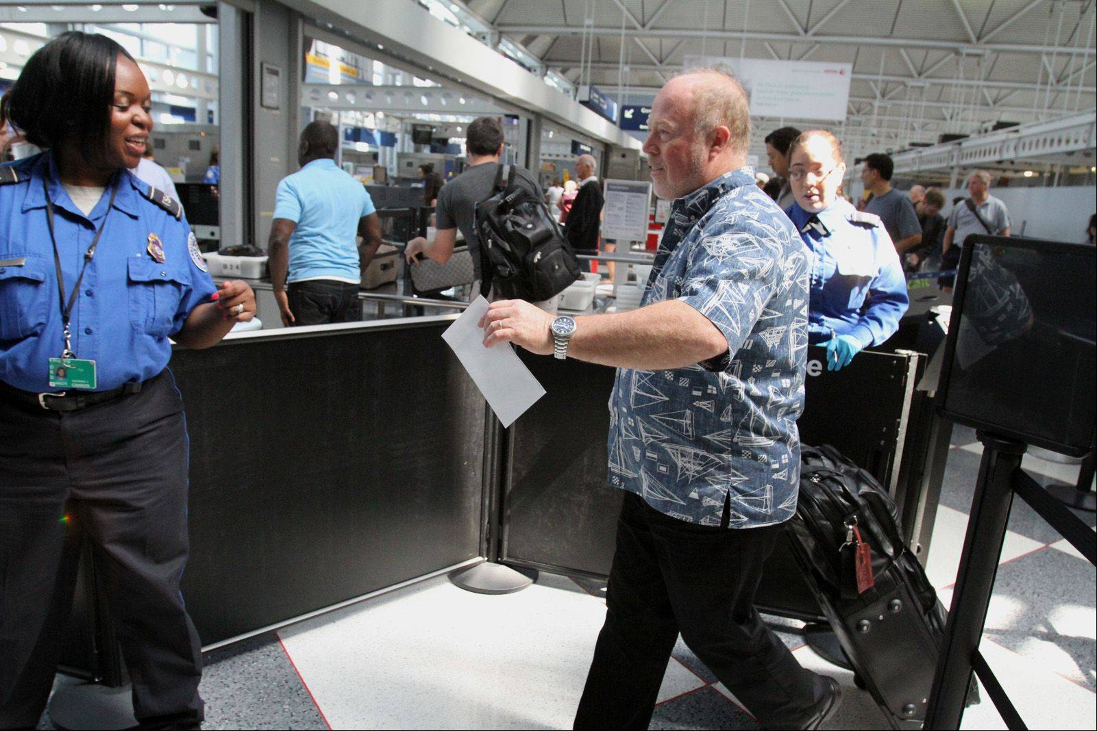 Laurent Perkin of San Diego goes through a new streamlined security checkpoint for preapproved travelers at the United Terminal at O'Hare International Airport in Chicago on Wednesday. Perkin was traveling home after business in Chicago.
