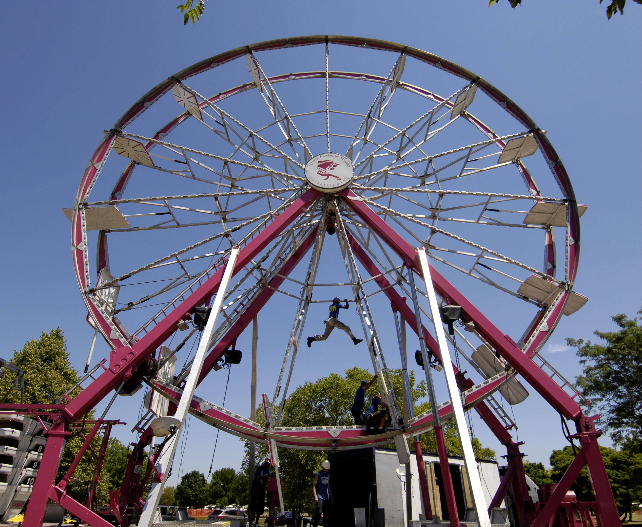 "Lenard ""Sarge"" James swings from one side to the other Tuesday as he and other workers set up the Ferris wheel for the 2012 Eyes to the Skies festival in Lisle. The carnival starts today."