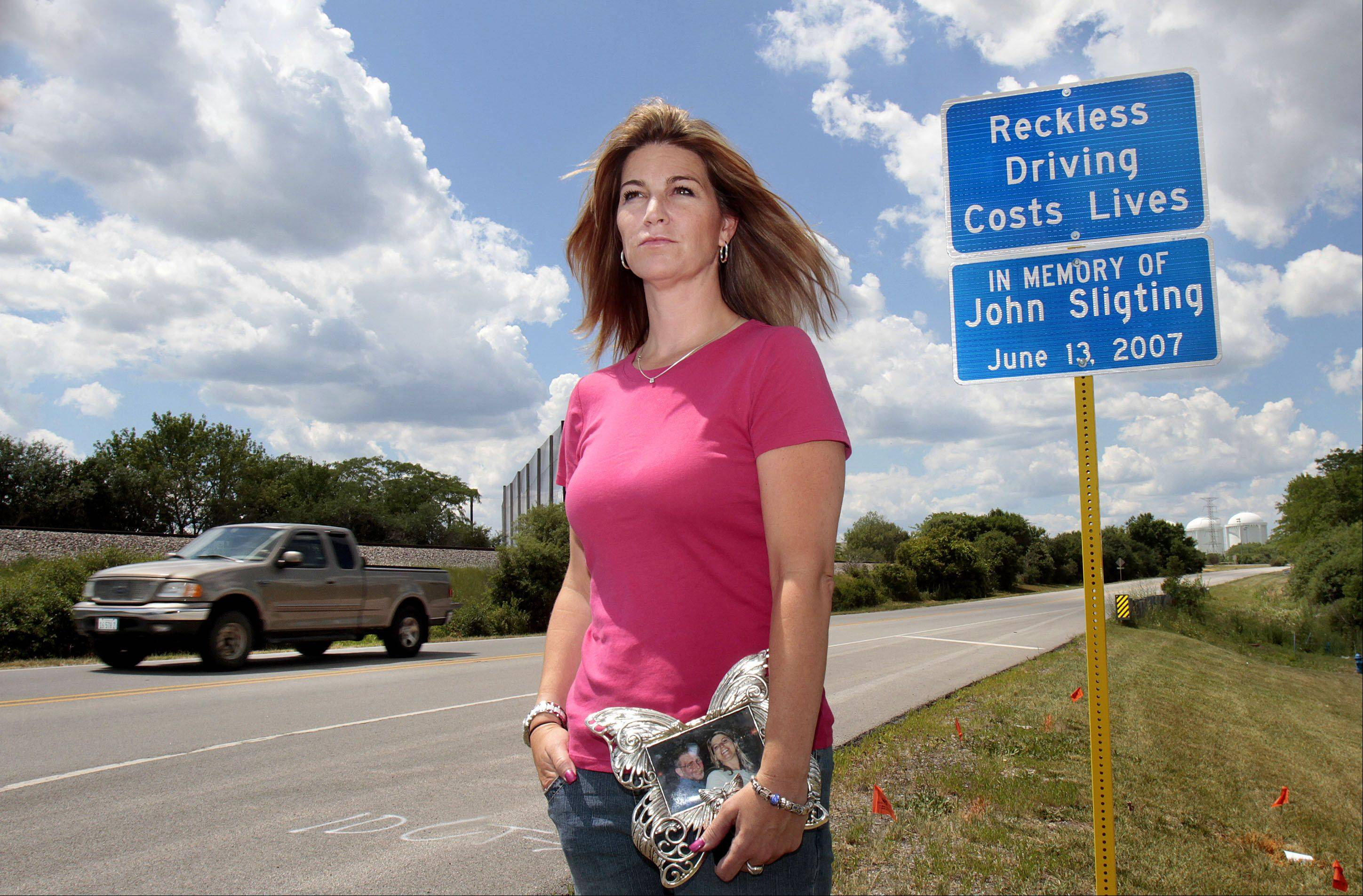 Charlene Sligting of Elgin holds a picture of her with her father, John, by signs recently installed by the Illinois Department of Transportation on Route 137 near Libertyville, where her father was killed in 2007.