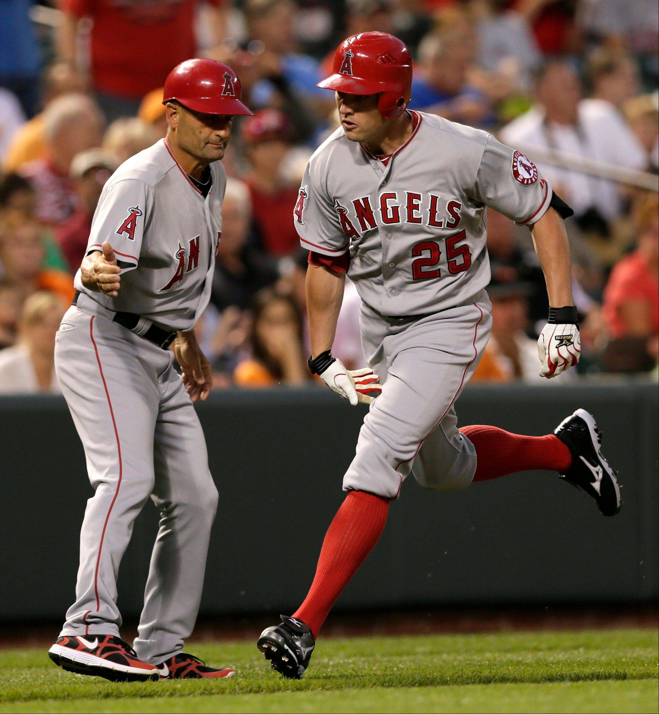 Los Angeles Angels third base coach Dino Ebel, left, high-fives Peter Bourjos as he rounds the bases after hitting a two-run homer in the sixth inning in Baltimore.