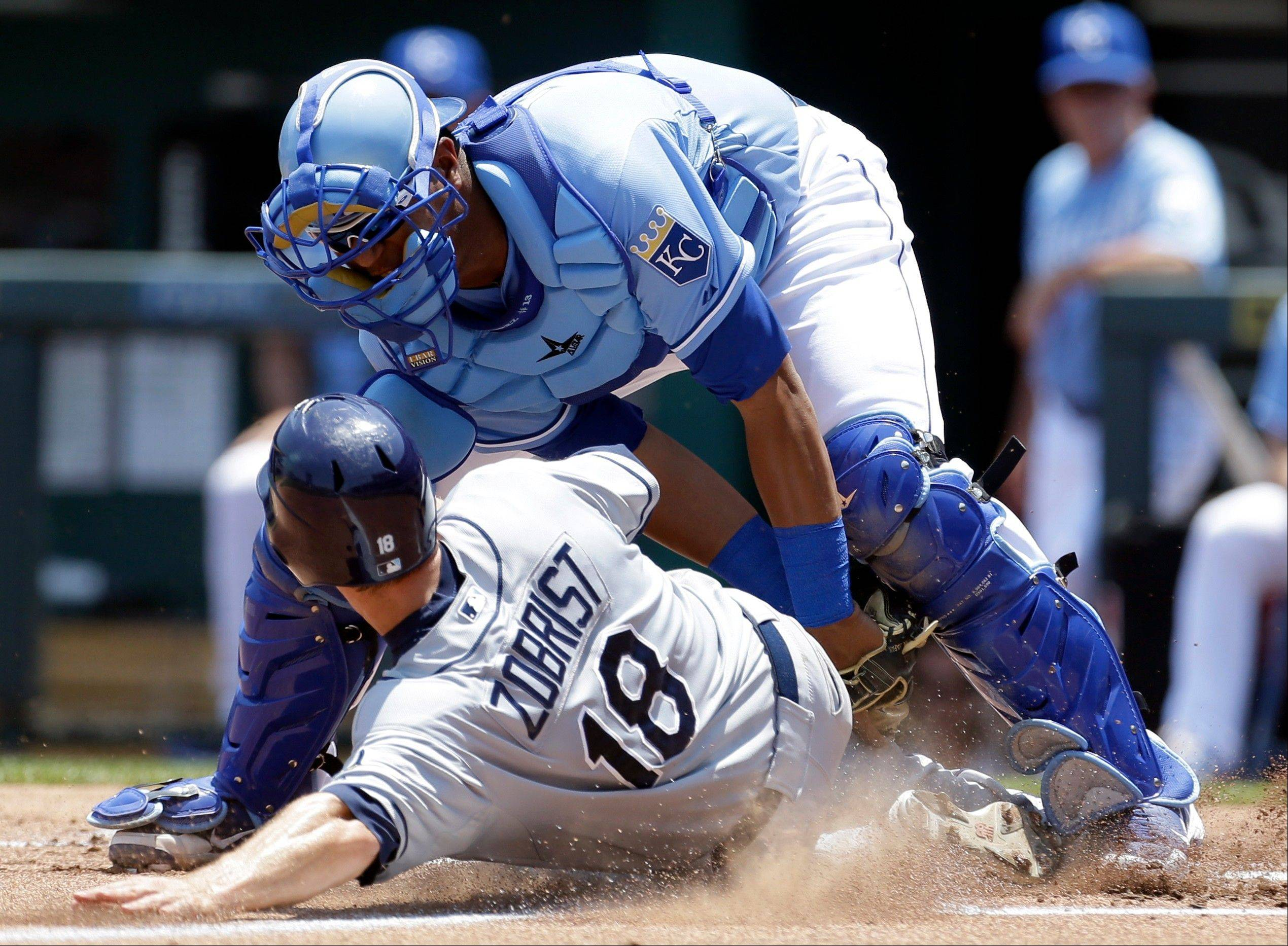 The Tampa Bay Rays' Ben Zobrist, bottom, is tagged out by Kansas City Royals catcher Salvador Perez while trying to score Wednesday during the second inning in Kansas City, Mo.
