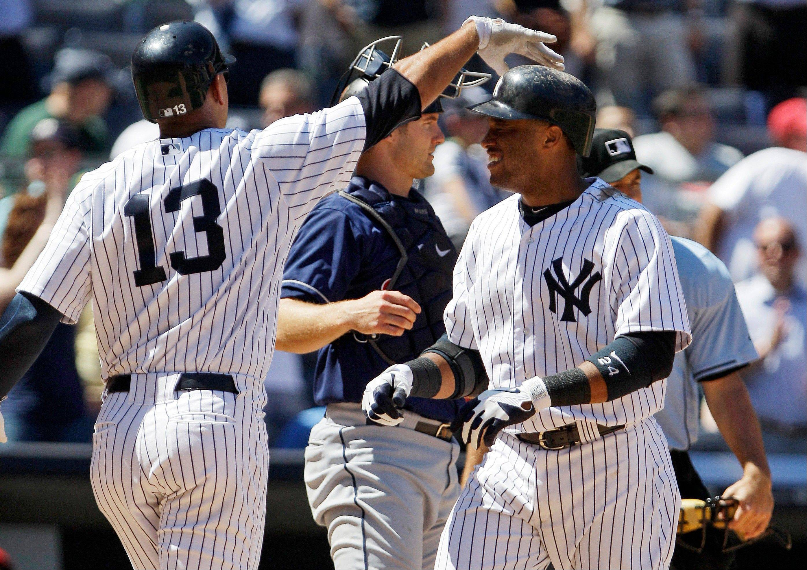 New York Yankees third baseman Alex Rodriguez celebrates with teammate Robinson Cano Wednesday after Cano hit a two-run home run during the sixth inning as Cleveland Indians catcher Lou Marson looks on in New York.