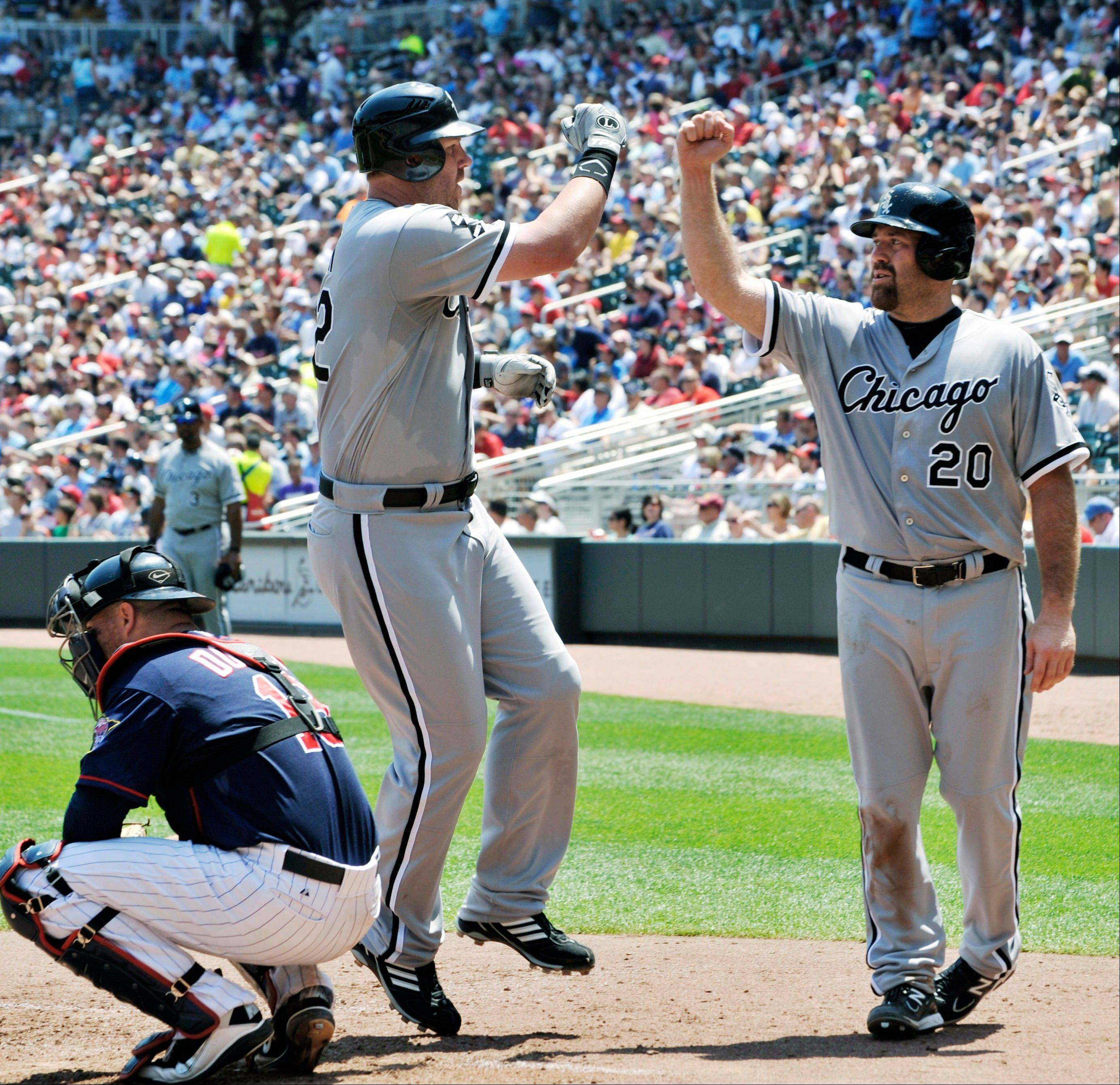 White Sox third baseman Kevin Youkilis, right, celebrates with Adam Dunn after Dunn's three-run home run off Minnesota Twins pitcher Nick Blackburn Wednesday during the fifth inning in Minneapolis. At left is Twins catcher Ryan Doumit.