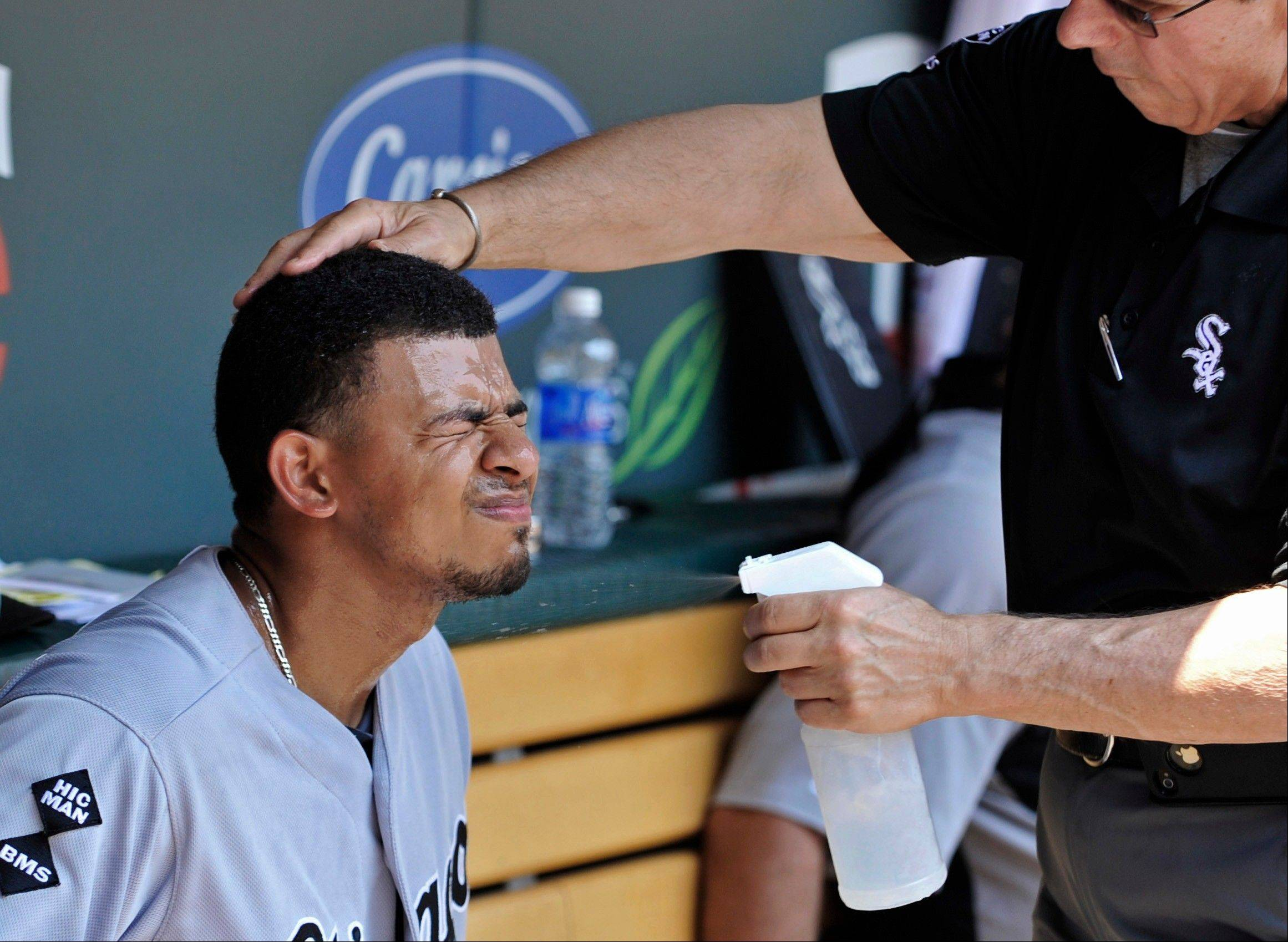 Eduardo Escobar closes his eyes as trainer Herm Schneider sprays him with cool water for relief from oppressive heat and high humidity during Wednesday's game in Minneapolis.