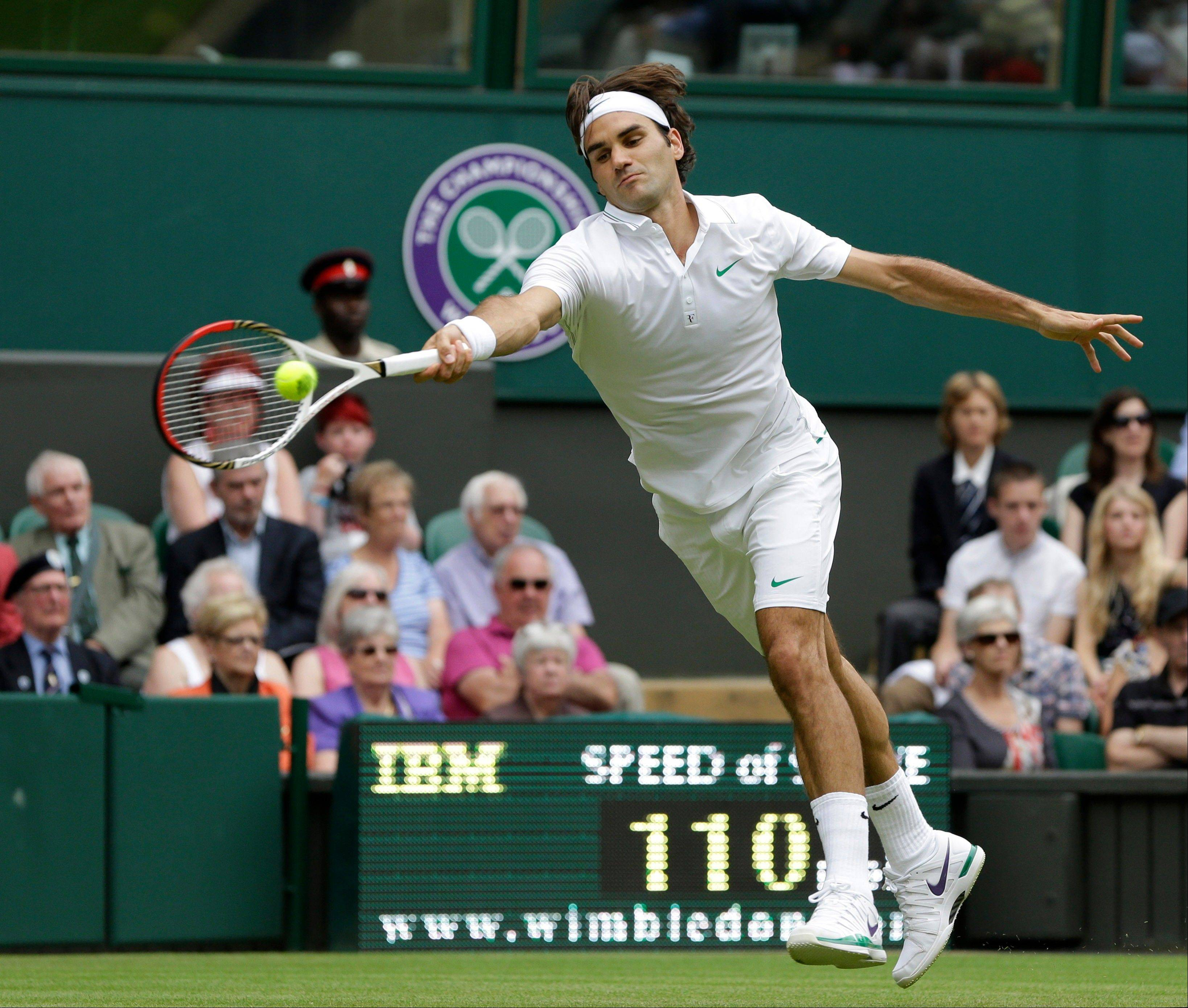Roger Federer returns a shot to Fabio Fognini Wednesday during a second round men's singles match at the All England Lawn Tennis Championships at Wimbledon, England.