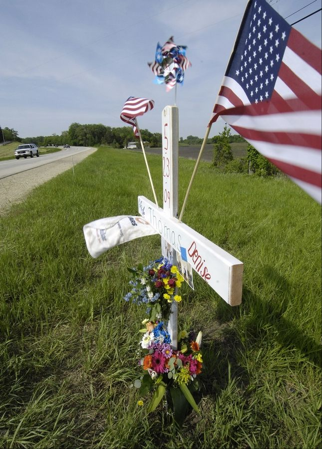 A wooden cross with American flags stands for Wade and Denise Thomas, who were killed in a multiple car and motorcycle crash on Route 47 at Smith Road, south of Elburn, in May 2009. Alia Bernard of Aurora is serving a seven-year sentence for causing the crash.