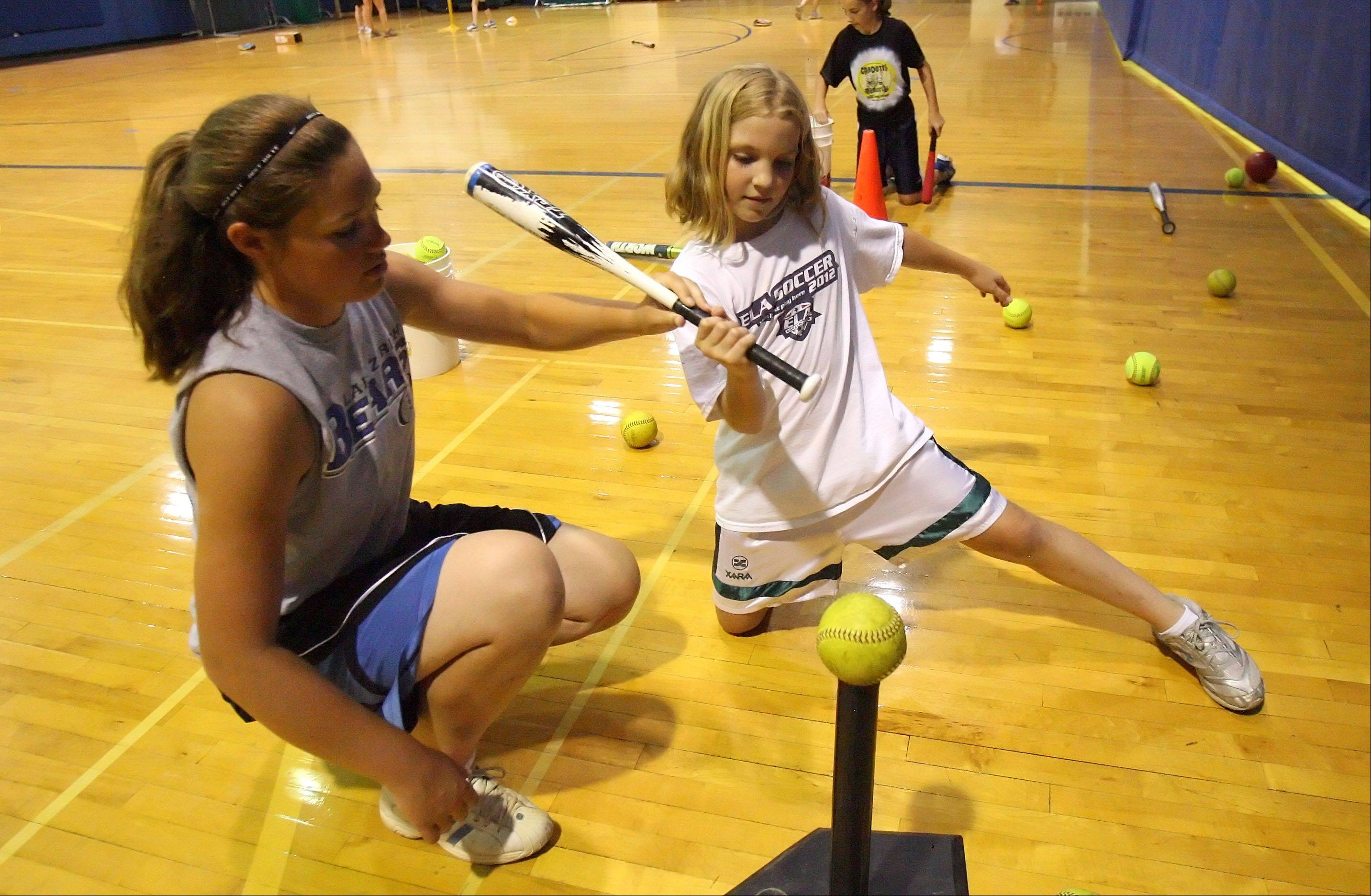 Softball instructor Christina Sandstedt goes through a drill with 9-year-old Nina Malak of Hawthorn Woods as the Lake Zurich High School softball camp went indoors to beat the heat Thursday.