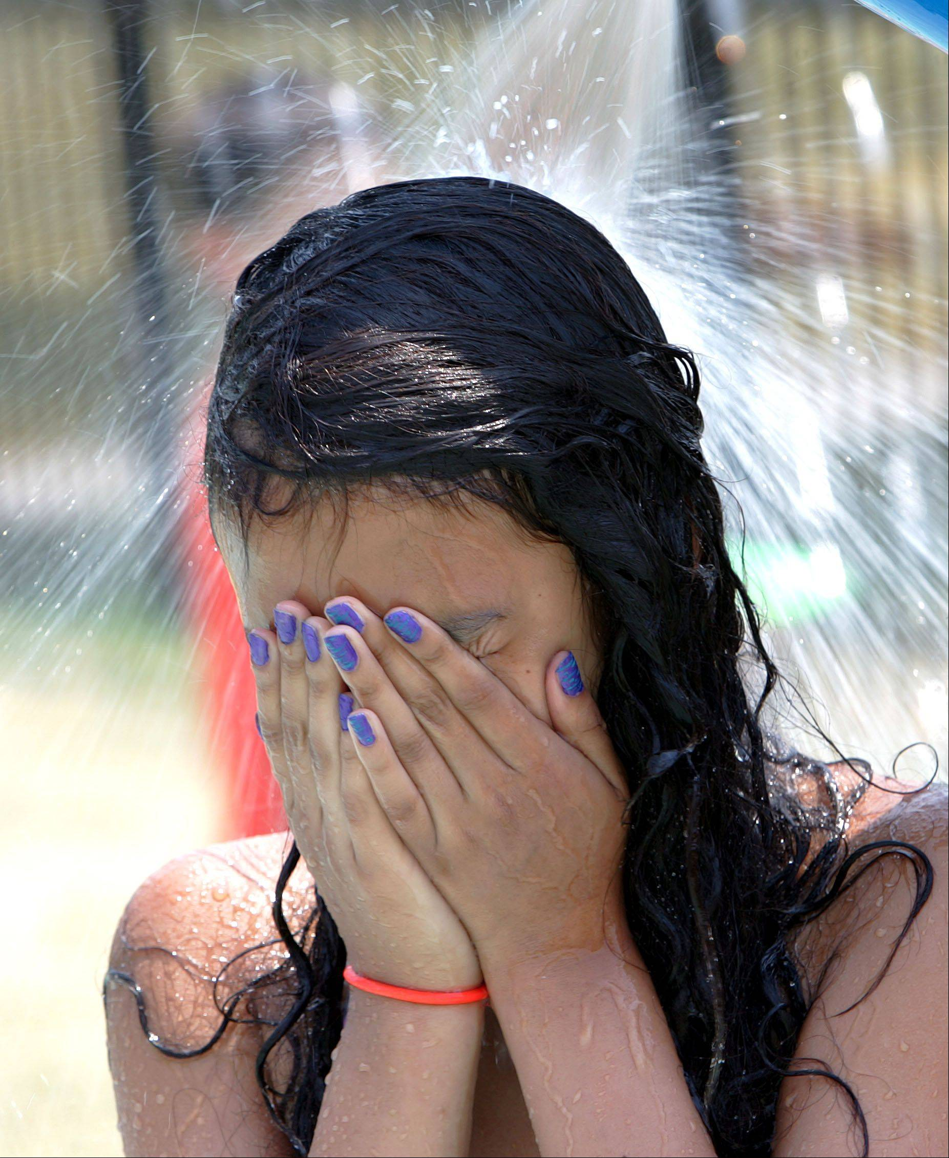 12-year-old Emilyn Najora of Round Lake Beach cools off at the Grayslake Park district spray park Thursday as temperatures climbed close to 100 degrees.