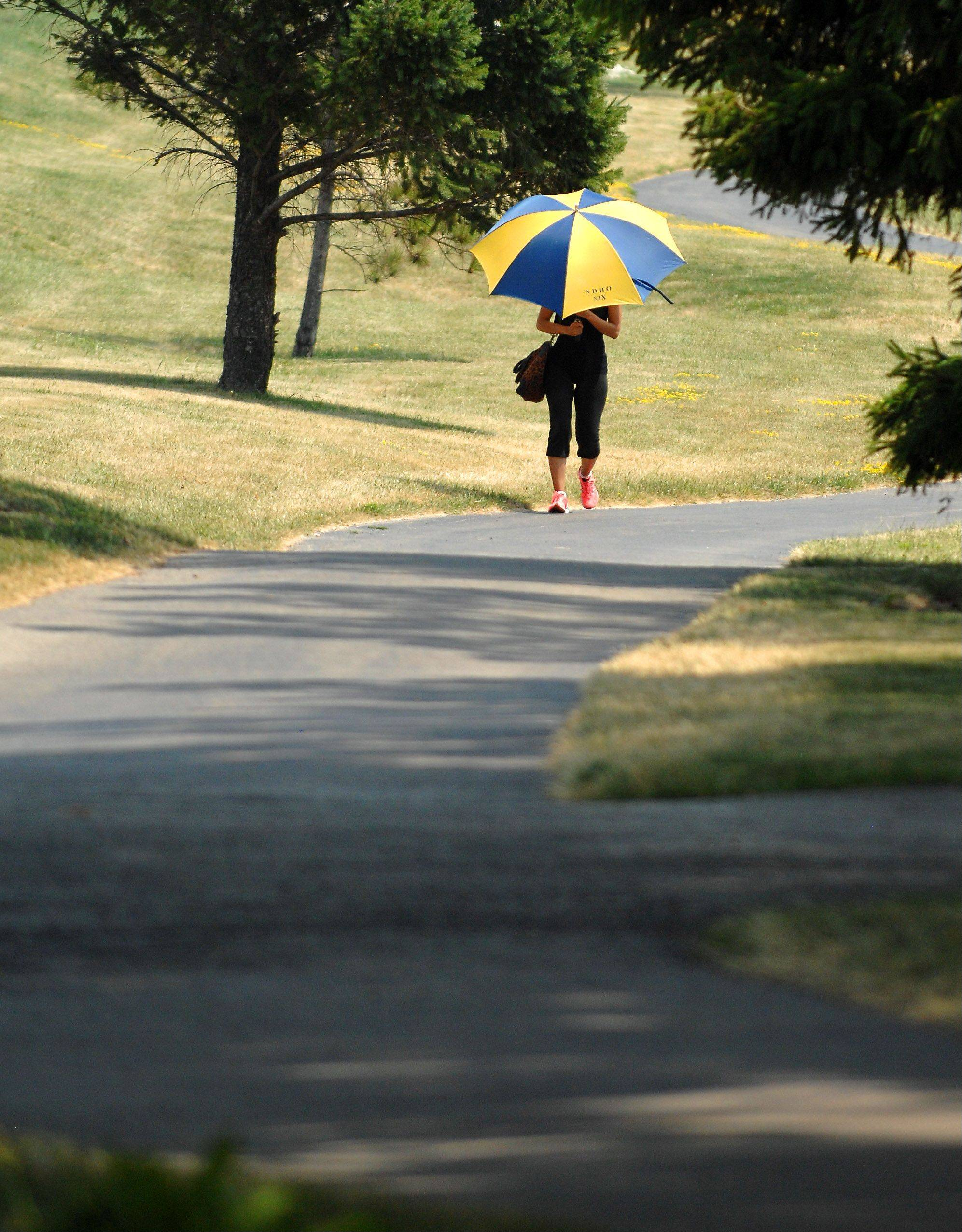 Charron Davis uses an umbrella to shield herself from the hot sun as she walks near Peck Farm Park in Geneva Thursday. Davis said she lives in Chicago but stays in Geneva for the summer.