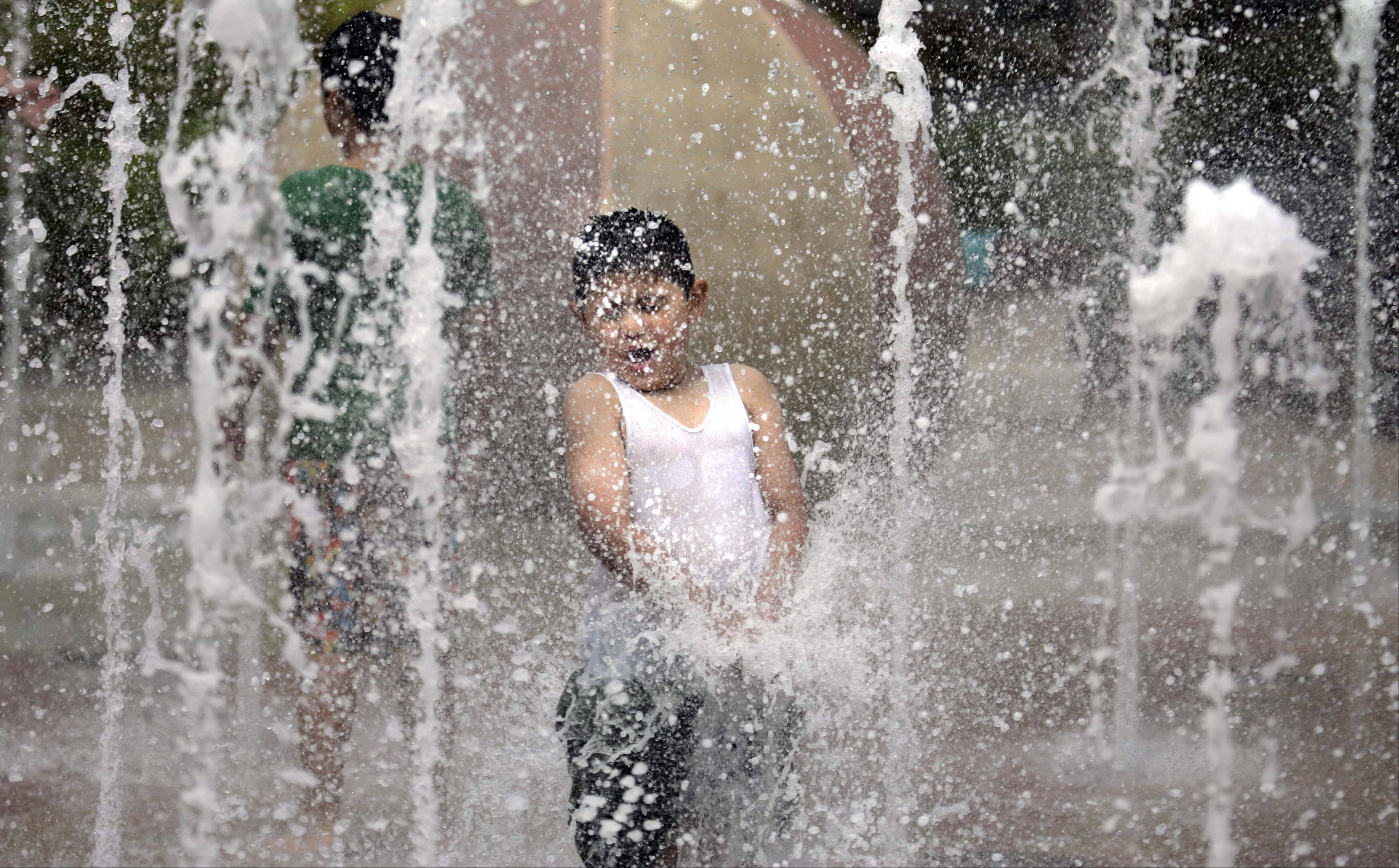 Omar Contreres, 5, of South Elgin, enjoys the water features at Festival Park in Elgin as Temperatures reached into the high 90s Thursday in the Fox Valley area.