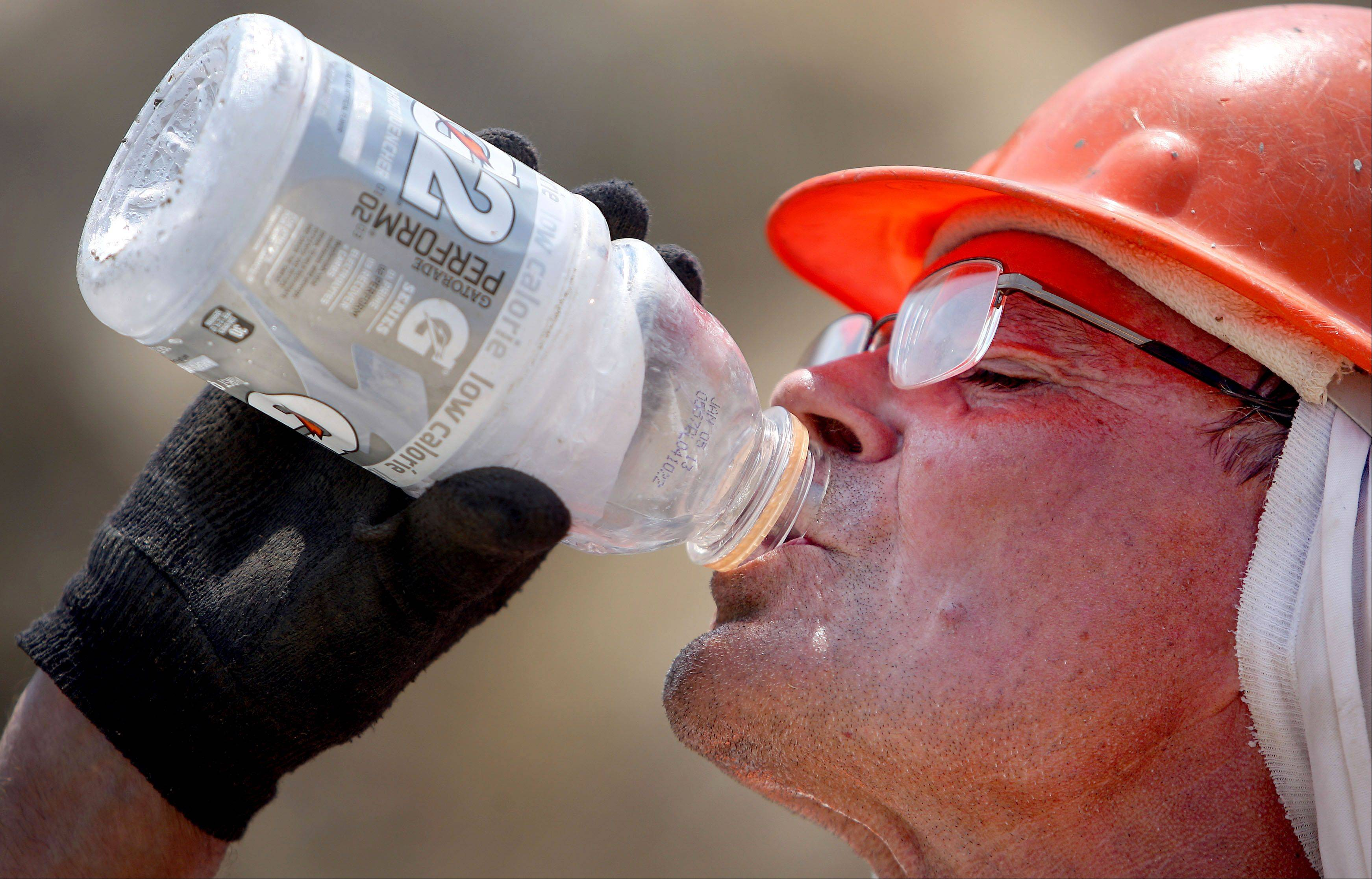 "Construction worker Bruce Burgett rehydrates after a long day in the heat while working on road construction on Route 176 near Wauconda Thursday. ""We started at 6 a.m. to beat the heat,"" said Burgett."