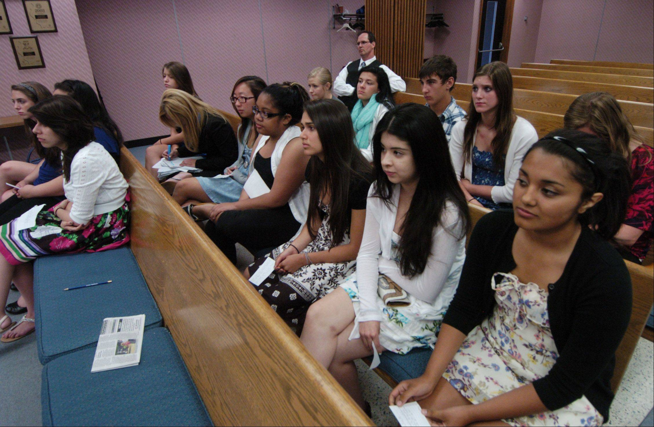 Jessica Vasquez, right, and Brenda Gomez, seated next to her, wait their turn as Maine West High School students ask questions of Des Plaines administrators during a news conference being televised live on the city cable channel.