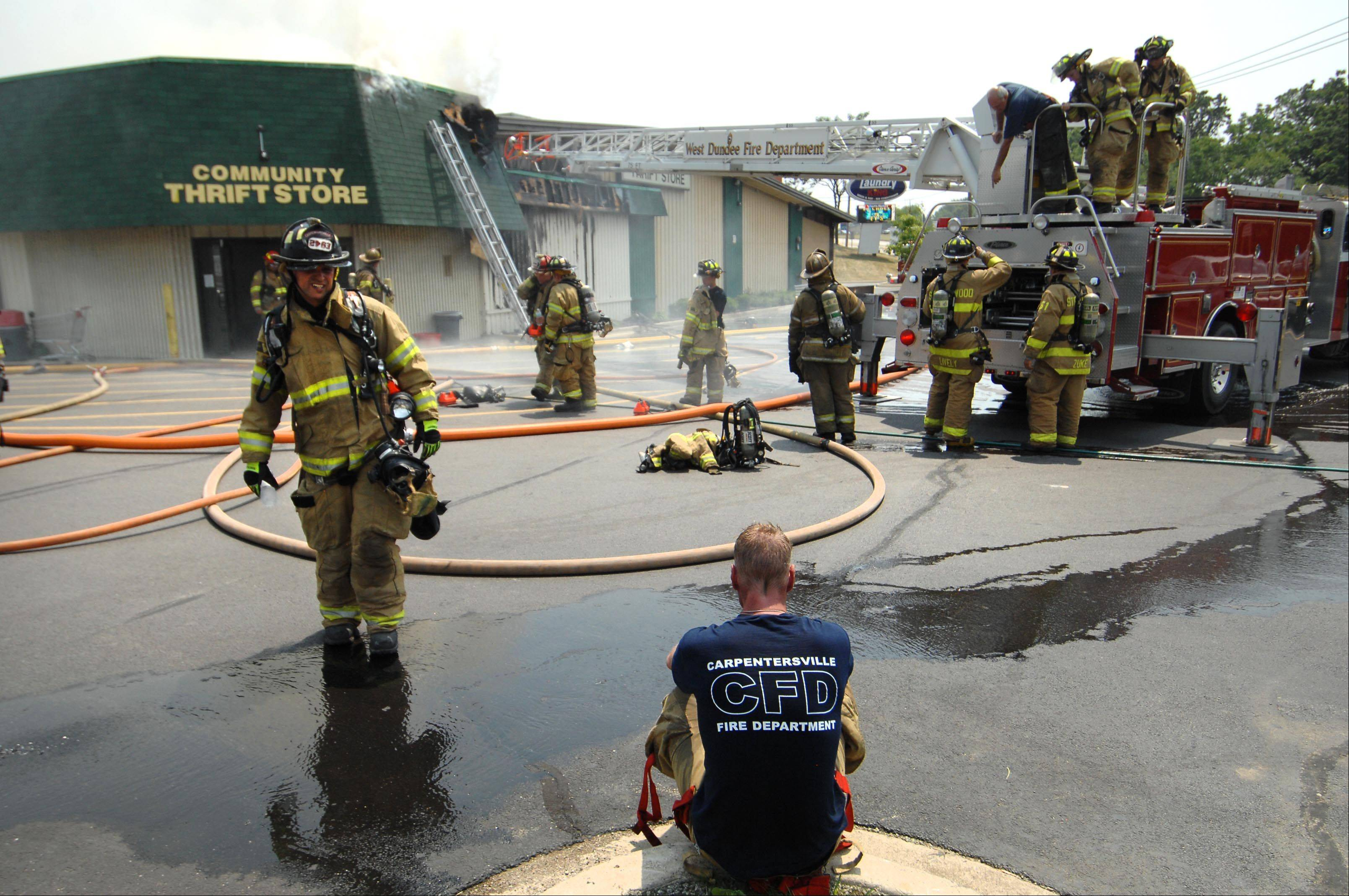 Carpentersville firefighter Eric Vogel rests on a curb as firefighters from several departments battle the heat and fire Thursday at Community Thrift Store in East Dundee.