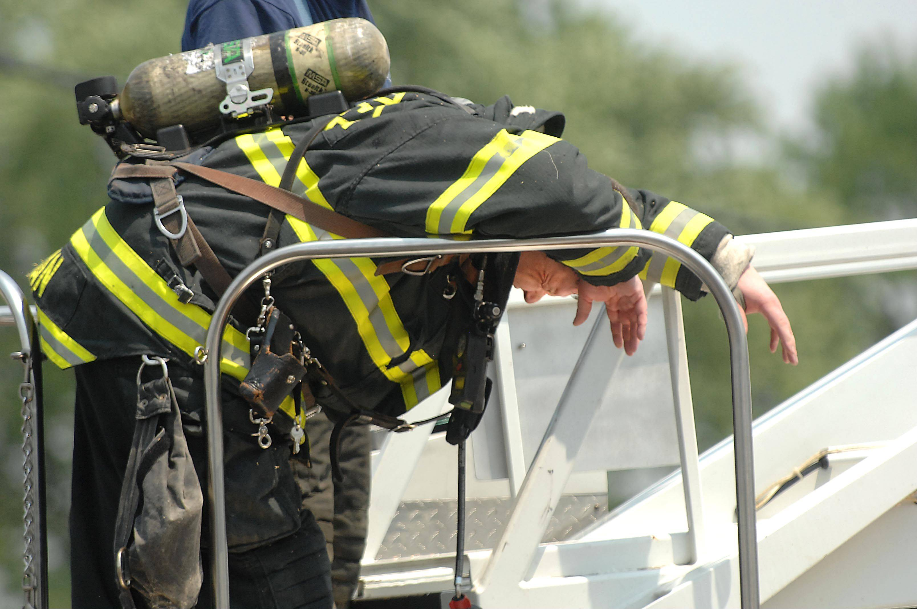 West Dundee firefighter Dan Kilian breaths deeply after working with a saw on a ladder as firefighters from several departments battled the heat and fire at Community Thrift Store in East Dundee Thursday afternoon. He came down from the ladder truck and went for treatment at a waiting ambulance.