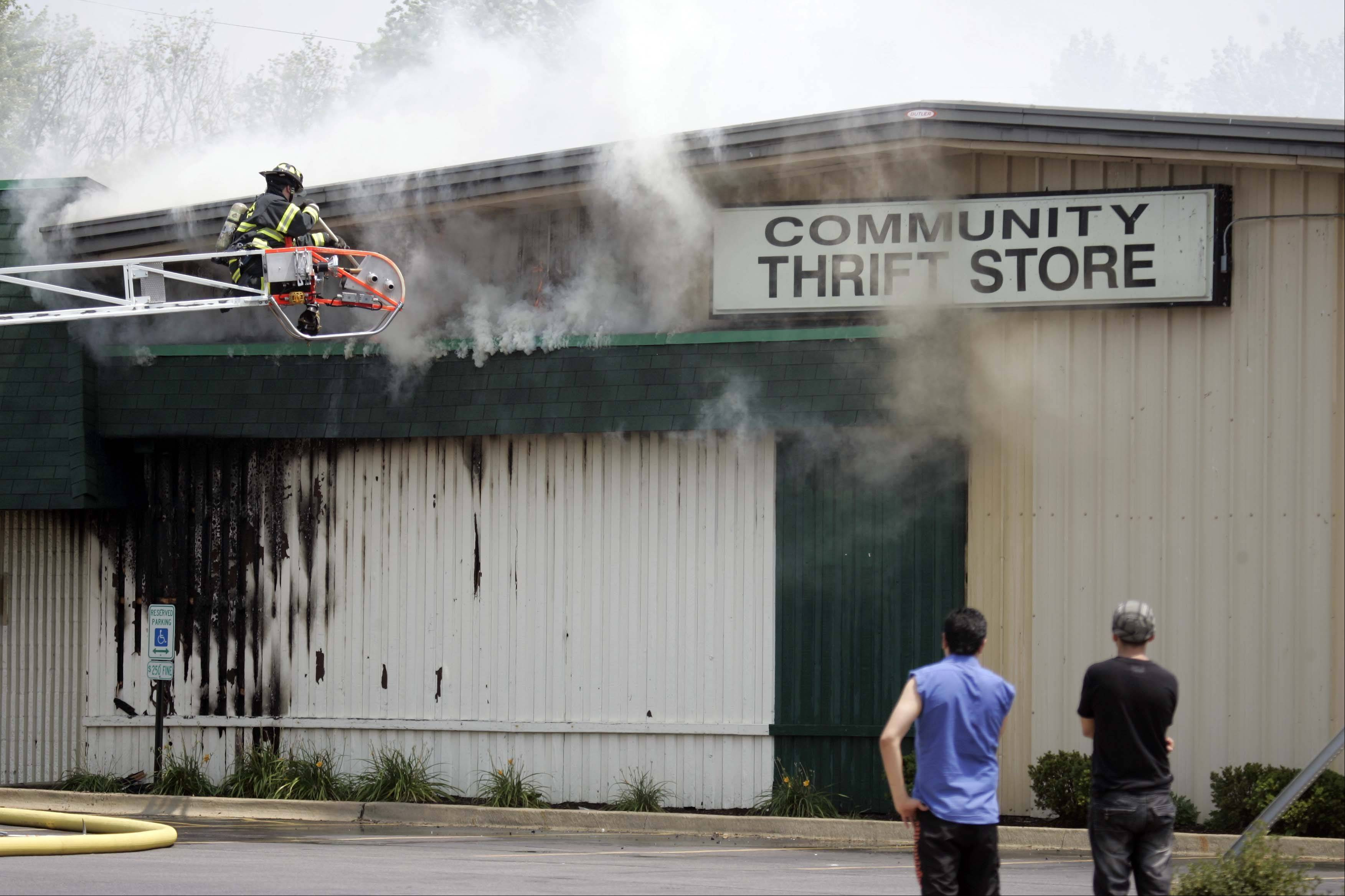 West Dundee firefighter Dan Kilian works to open the roof line as East Dundee, West Dundee, Carpentersville, Barrington, Elgin, South Elgin and numerous regional departments responded to a fire at the Community Thrift Store Thursday.