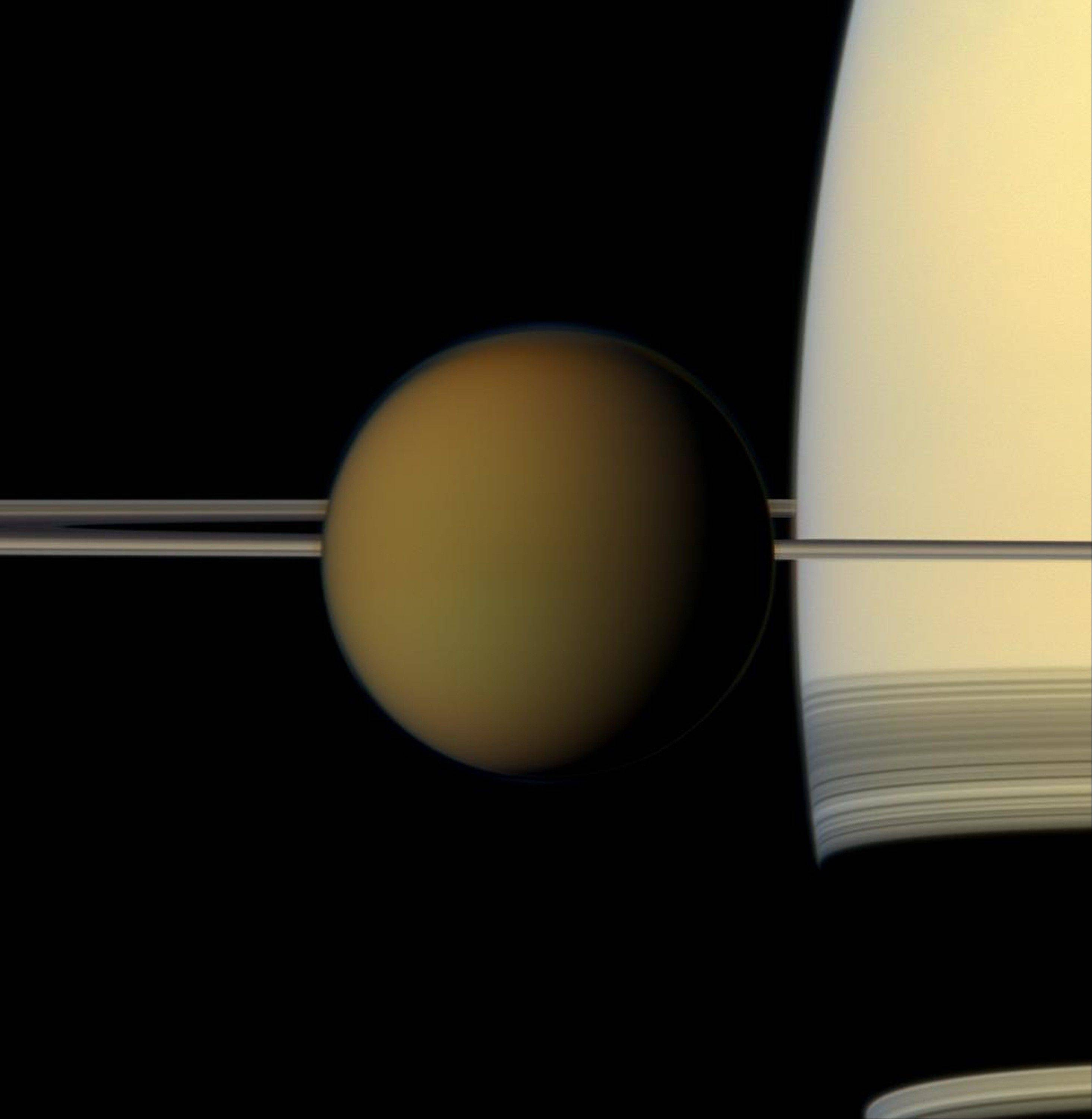 This undated true color image by the Cassini spacecraft released by NASA shows Saturn's largest moon, Titan, passing in front of the planet and its rings. A new study released Thursday suggests there may be an ocean below Titan's frigid surface.