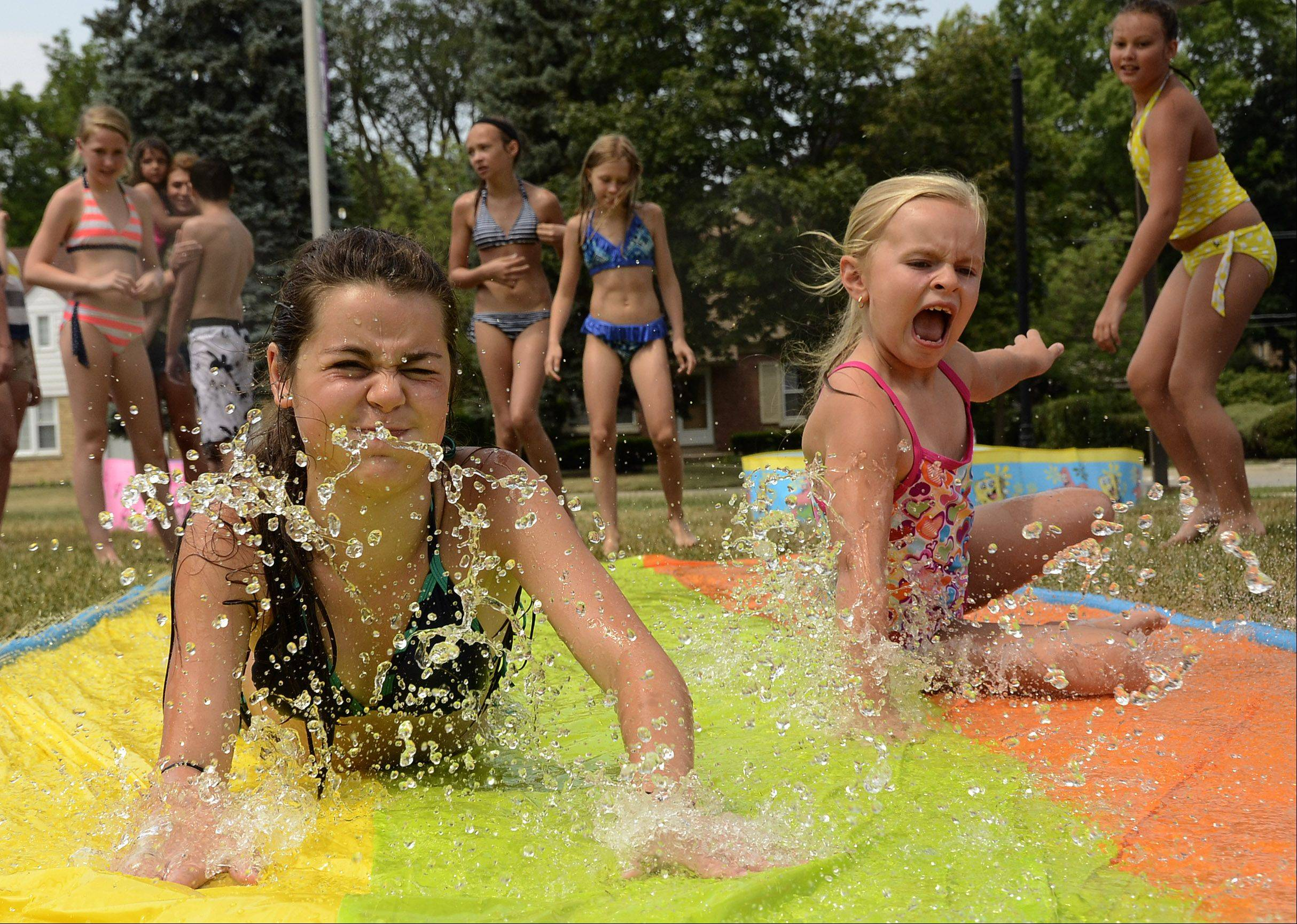 Bill Zars/bzars@dailyherald.com Gabi Aranza, 11, of Hoffman Estates, left, and Adrina Lee, 6, of Schaumburg cool off during theater camp at Faith Lutheran Church in Arlington Heights Thursday as the temperature threatens to his 100 degrees.
