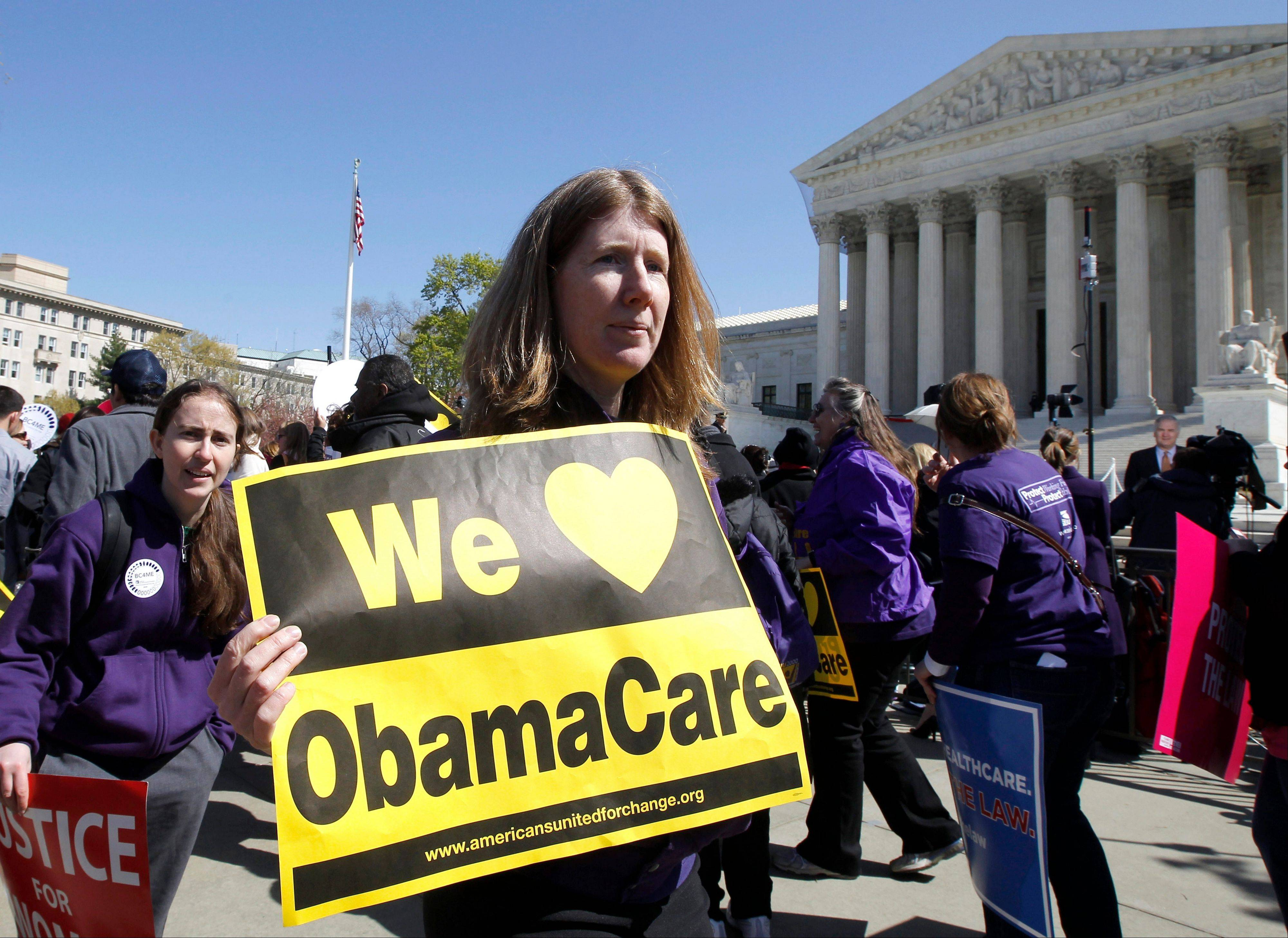 "Holding a sign saying ""We Love ObamaCare"" supporters of health care reform rally in front of the Supreme Court in Washington in March."
