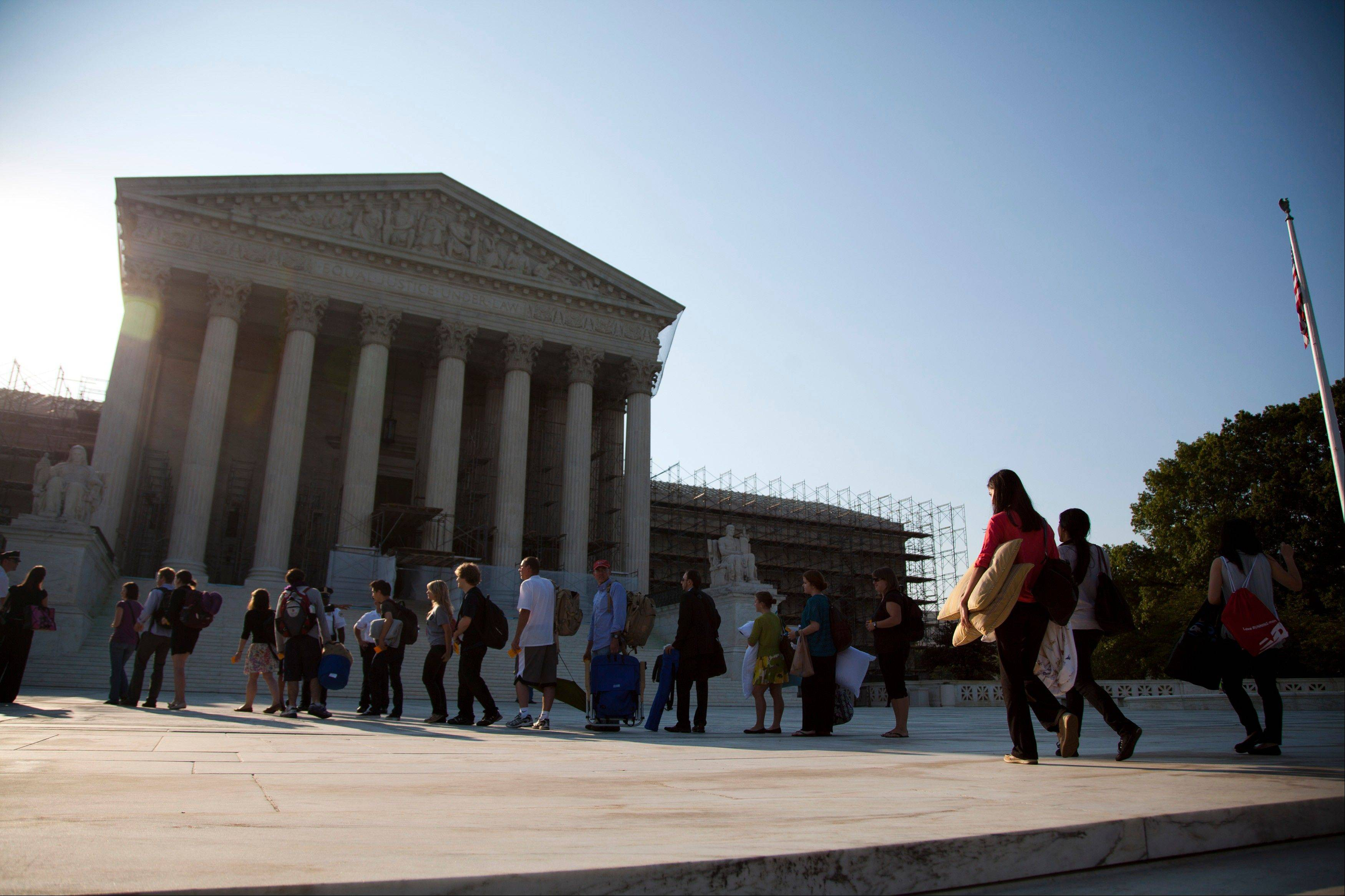 People who waited in line overnight to hear the Supreme Court on a landmark case on health care hold their belongings as they make their way into the court in Washington, Thursday, June 28, 2012.