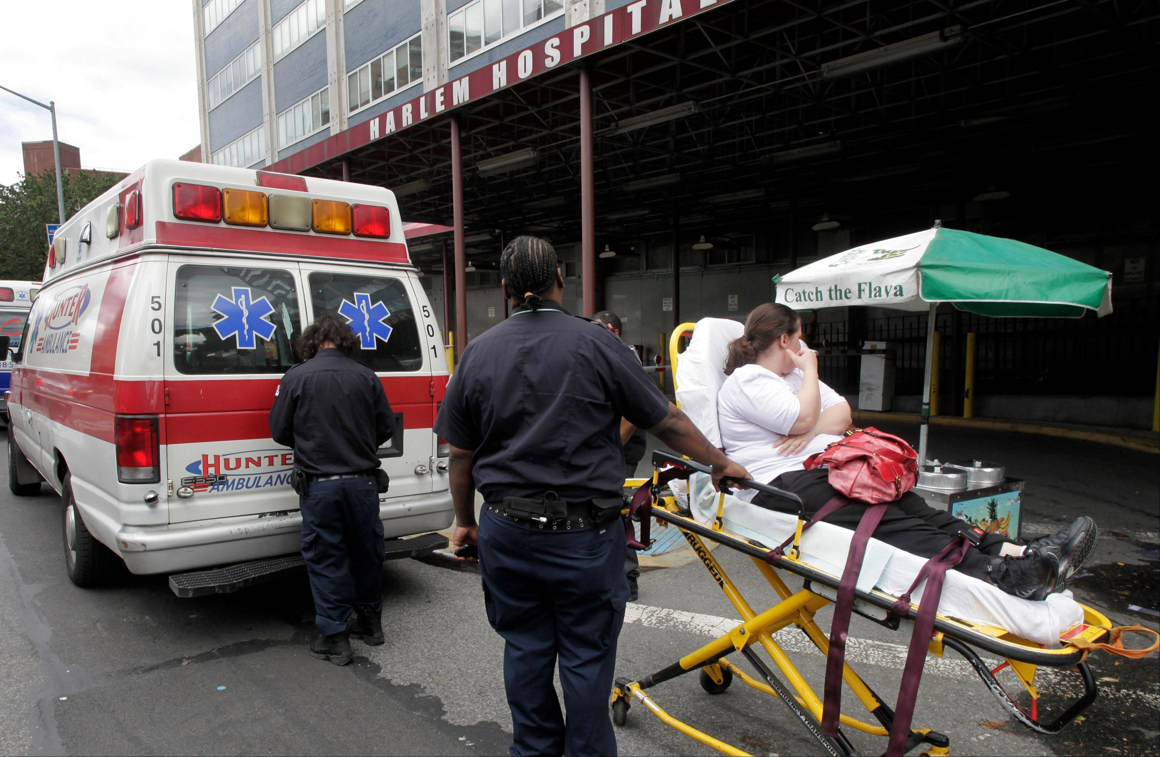 In this Tuesday, June 26, 2012 photo, a woman on a stretcher is wheeled to an ambulance as she leaves Harlem Hospital in New York. The Supreme Court is expected to rule on the constitutionality of Obama's health care overhaul Thursday, June 28.