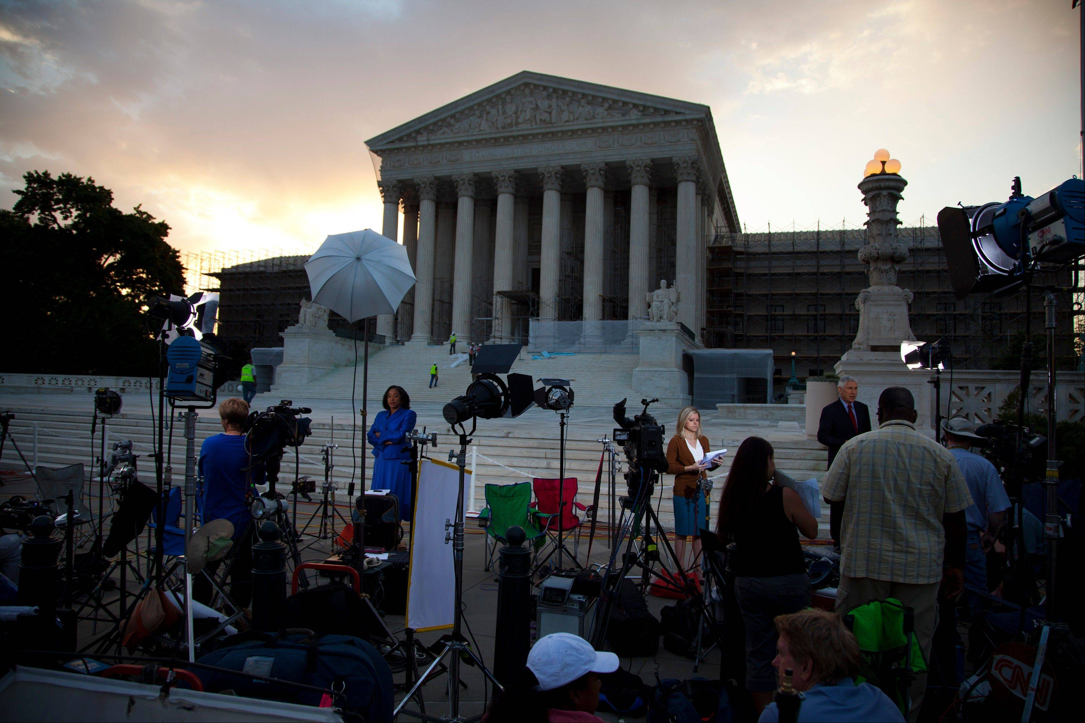 Journalists wait outside the Supreme Court for a landmark decision on health care on Thursday, June 28, 2012 in Washington.