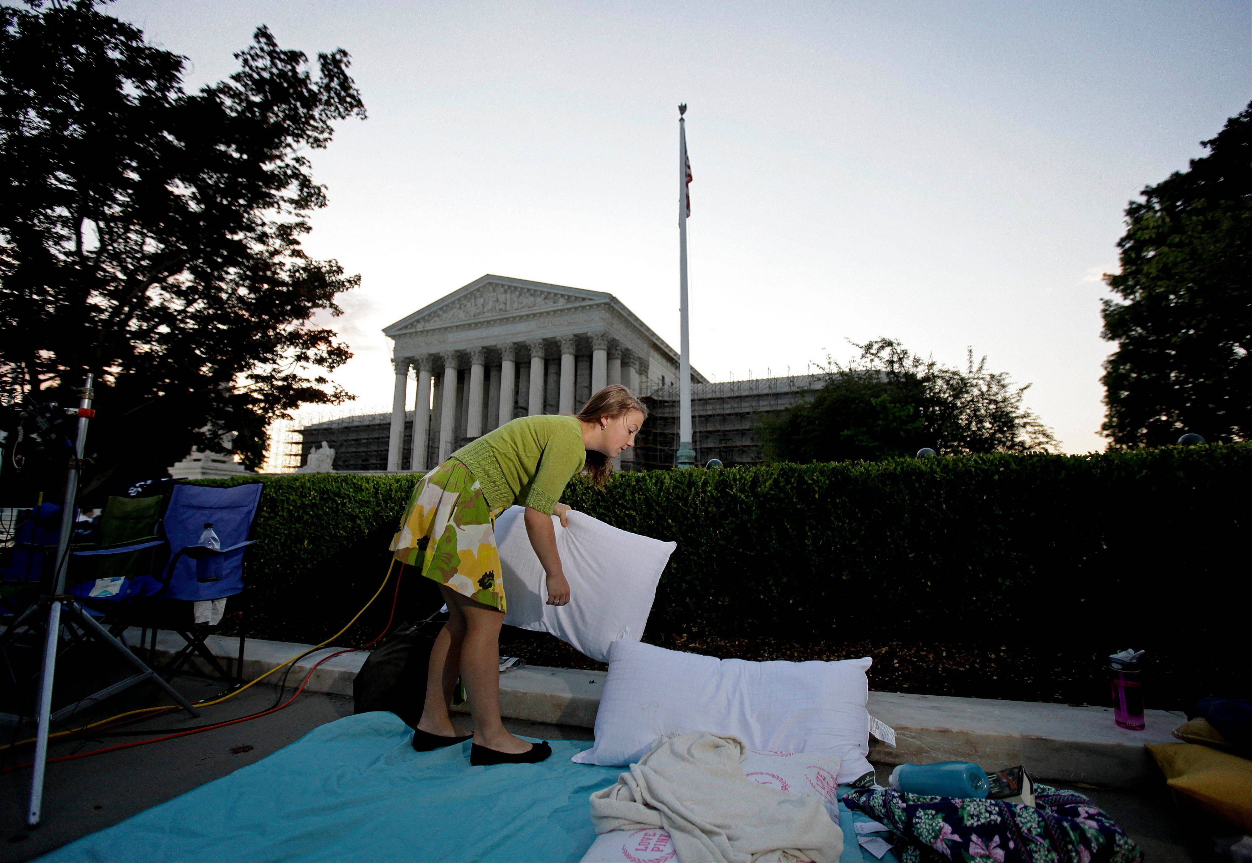 Maggie O'Brien, 20, of Syracuse, N.Y., wakes up after spending the night sleeping outside the Supreme Court Thursday, June 28, 2012, in Washington. Saving its biggest case for last, the Supreme Court is expected to announce its verdict Thursday on President Barack Obama's health care law.