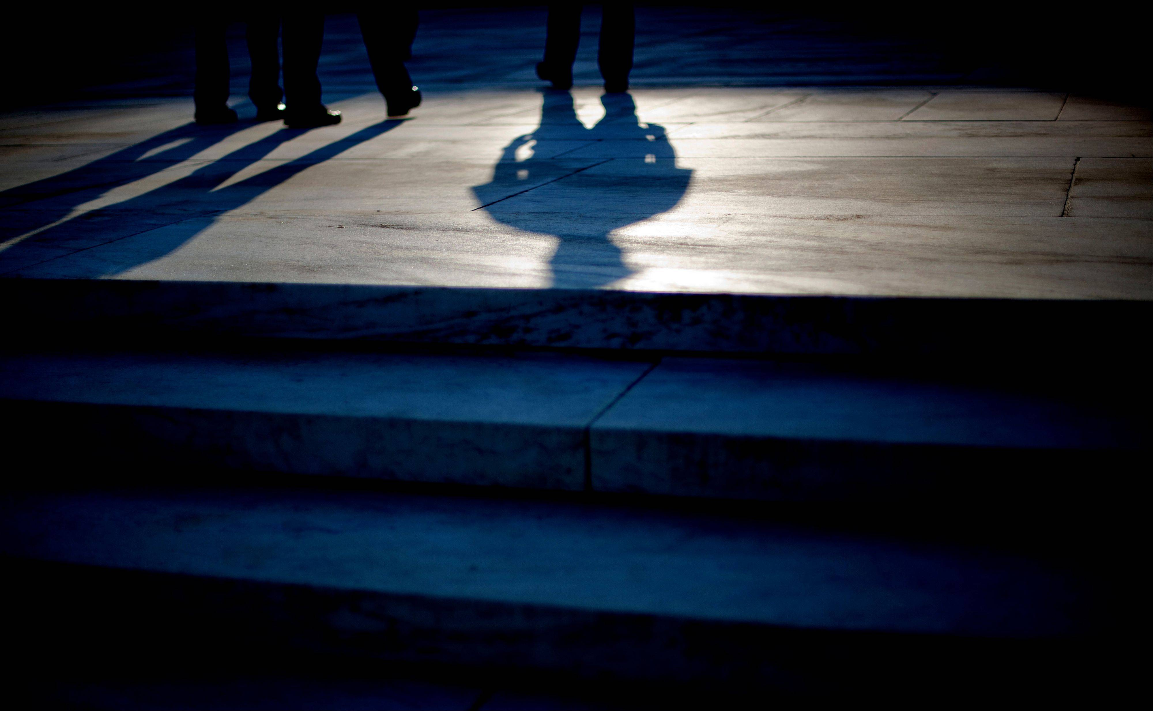 The shadow of an officer is cast as he stands guard on the steps of the Supreme Court in Washington, Thursday, June 28, 2012. Saving its biggest case for last, the Supreme Court is expected to rule on President Barack Obama's health care law.