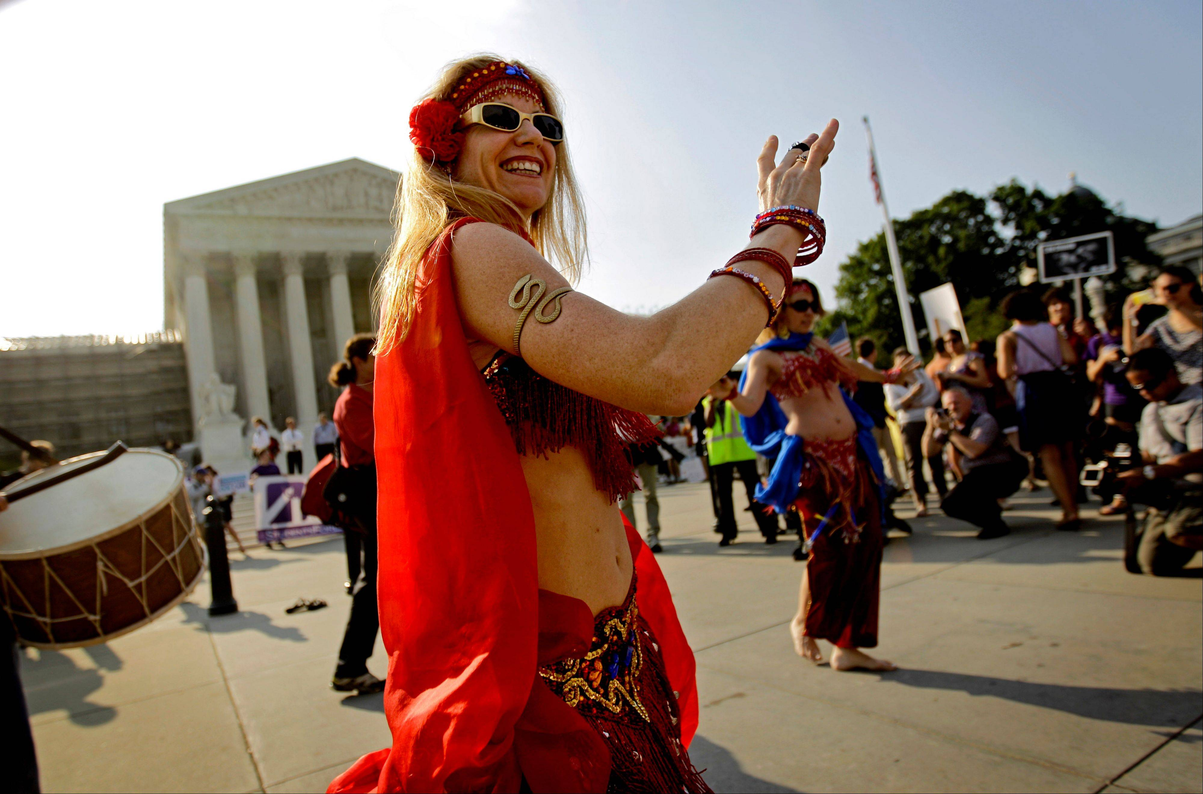 Belly dancer Jennifer Carpenter-Peak of Washington, dances outside the Supreme Court in Washington,Thursday, June 28, 2012, as the Supreme Court is expected to announce its ruling on President Barack Obama's health care law.