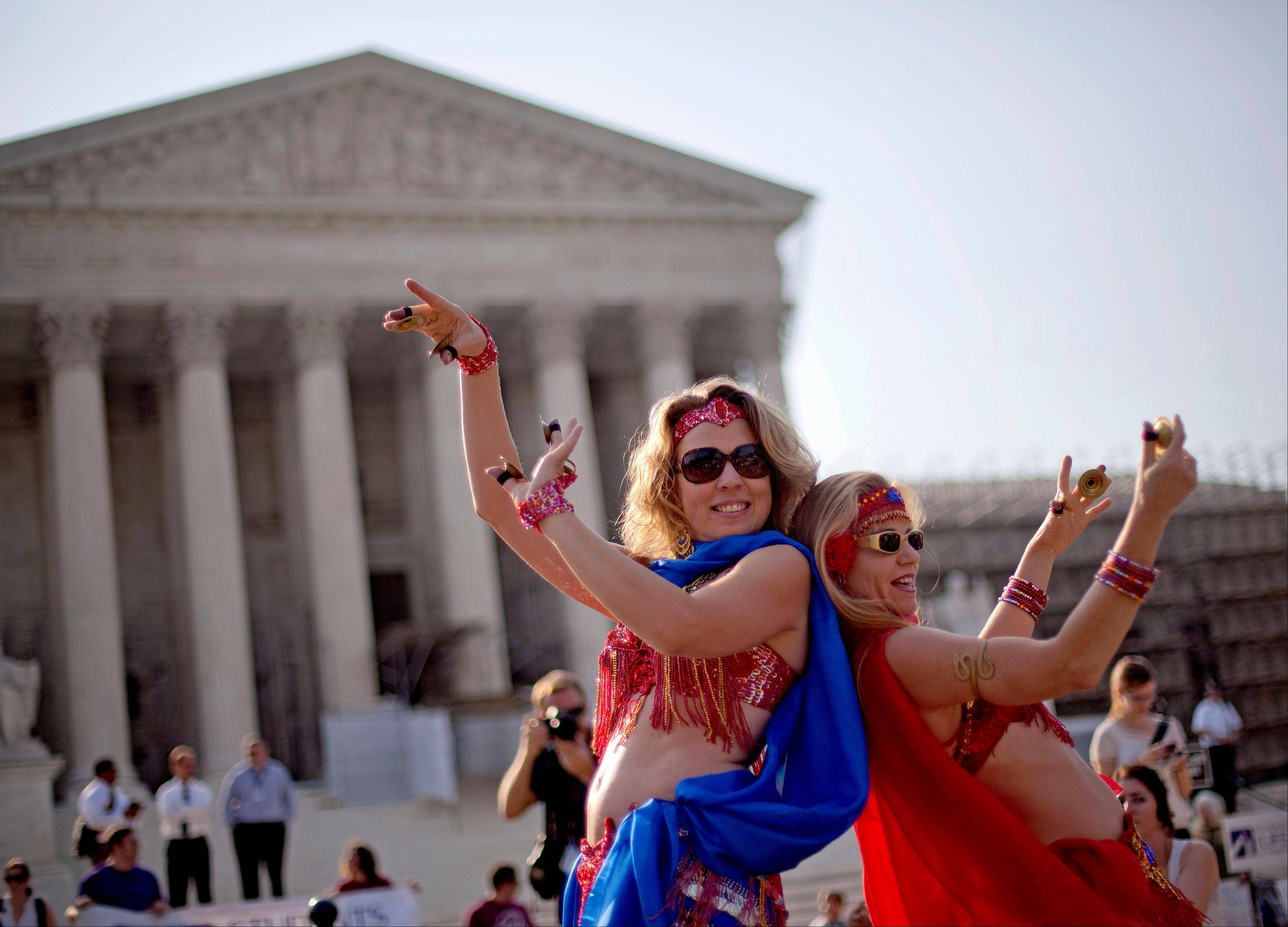 Belly dancers Angela Petry, left, and Jennifer Carpenter-Peak, both of Washington, dance outside the Supreme Court in Washington,Thursday, June 28, 2012, in Washington, as part of a demonstration as the Supreme Court is expected to rule on President Barack Obama's health care law.