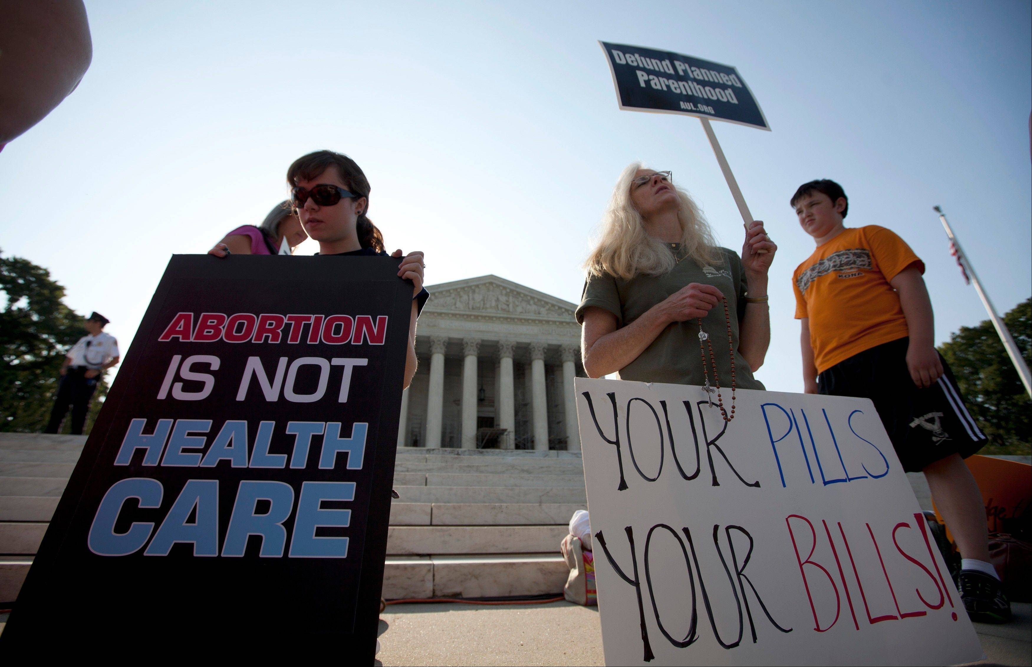Demonstrators pray outside the Supreme Court in Washington, Thursday, June 28, 2012, before a landmark decision on health care.