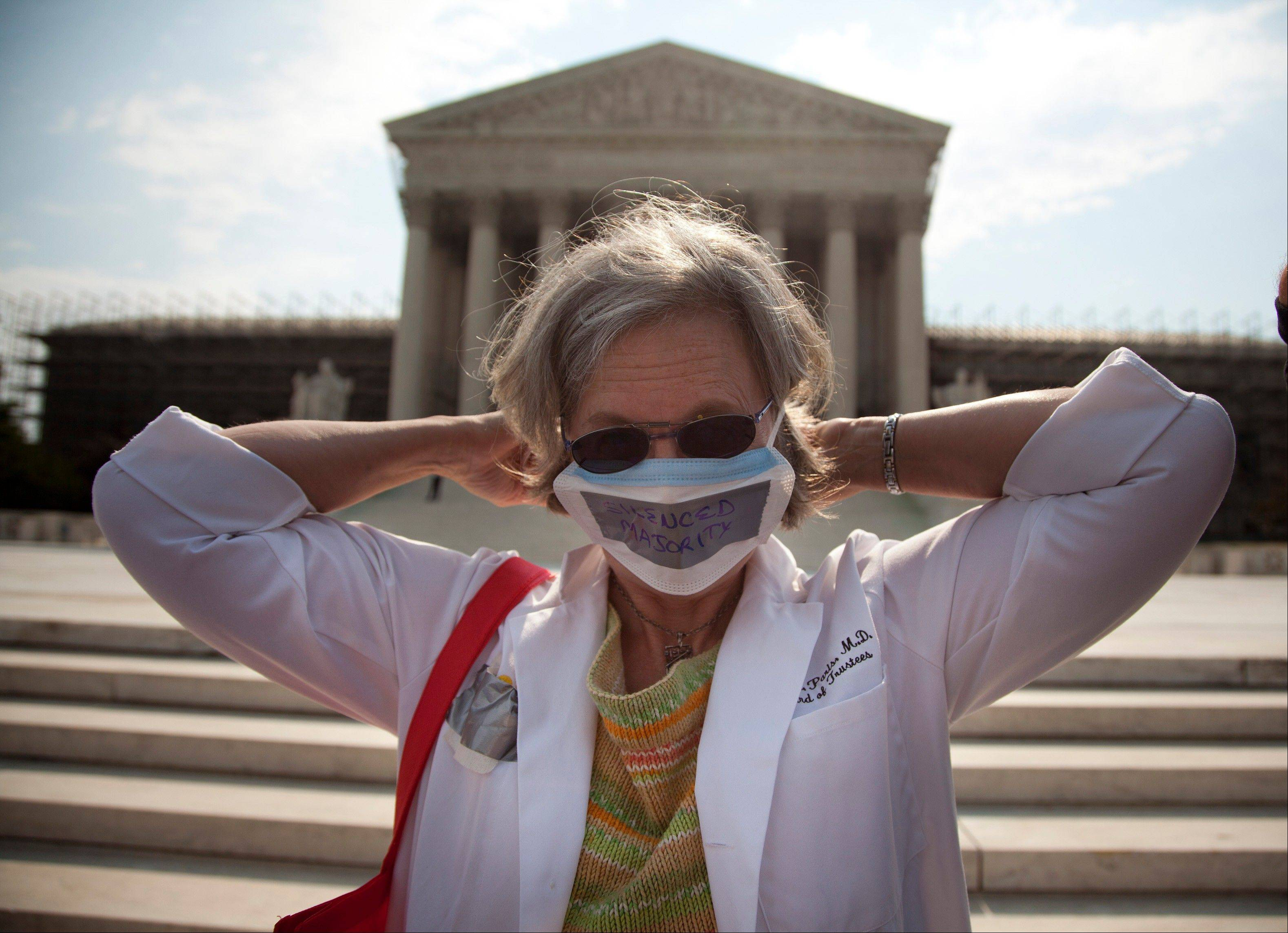 Carol Paris of Leonardtown, Md. demonstrates outside the Supreme Court in Washington. On Thursday the Supreme Court will deliver their ruling on President Barack Obama's health care package.