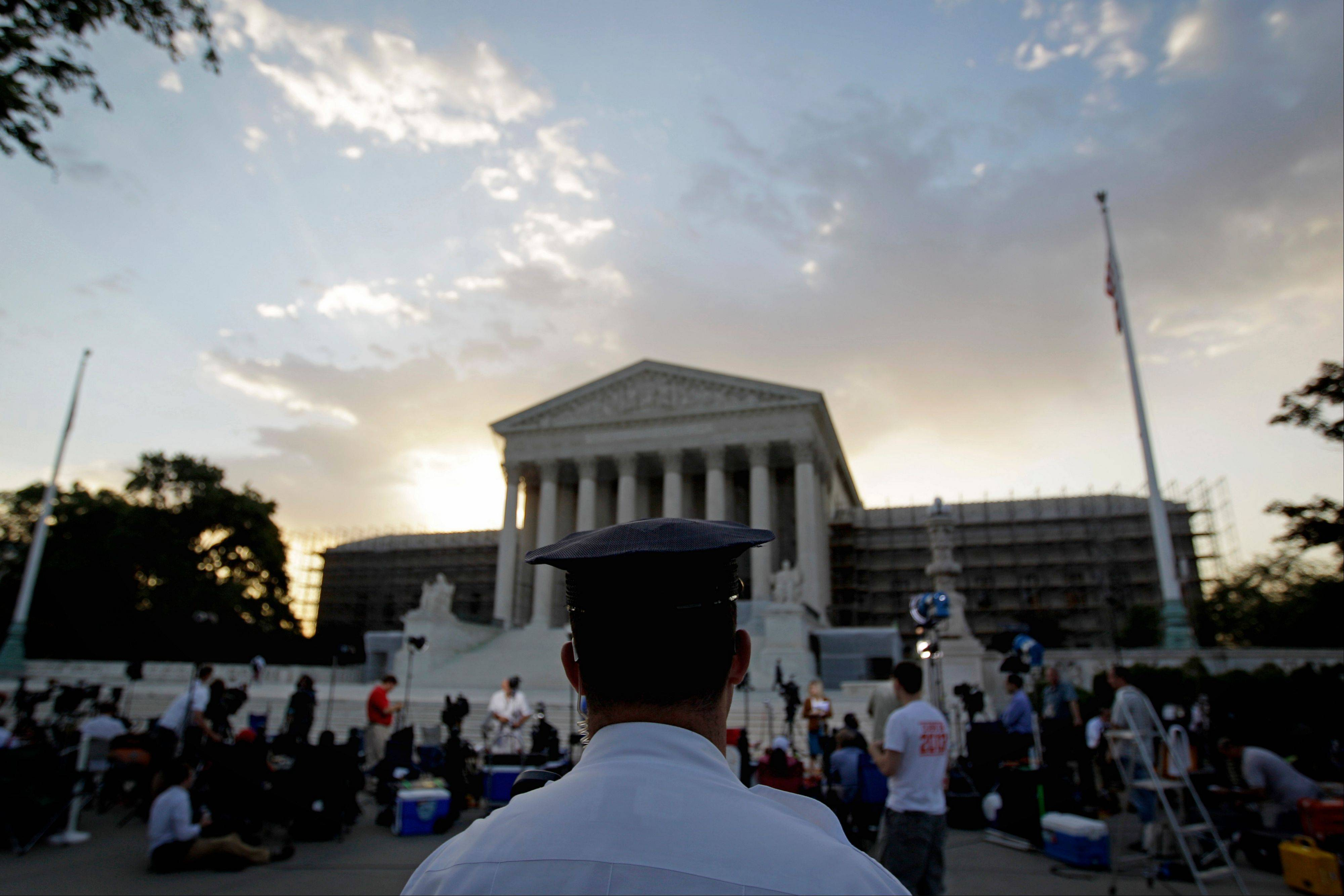 An officer stands outside the Supreme Court as media and the public gather Thursday, June 28, 2012, in Washington. Saving its biggest case for last, the Supreme Court is expected to announce its verdict Thursday on President Barack Obama's health care law.
