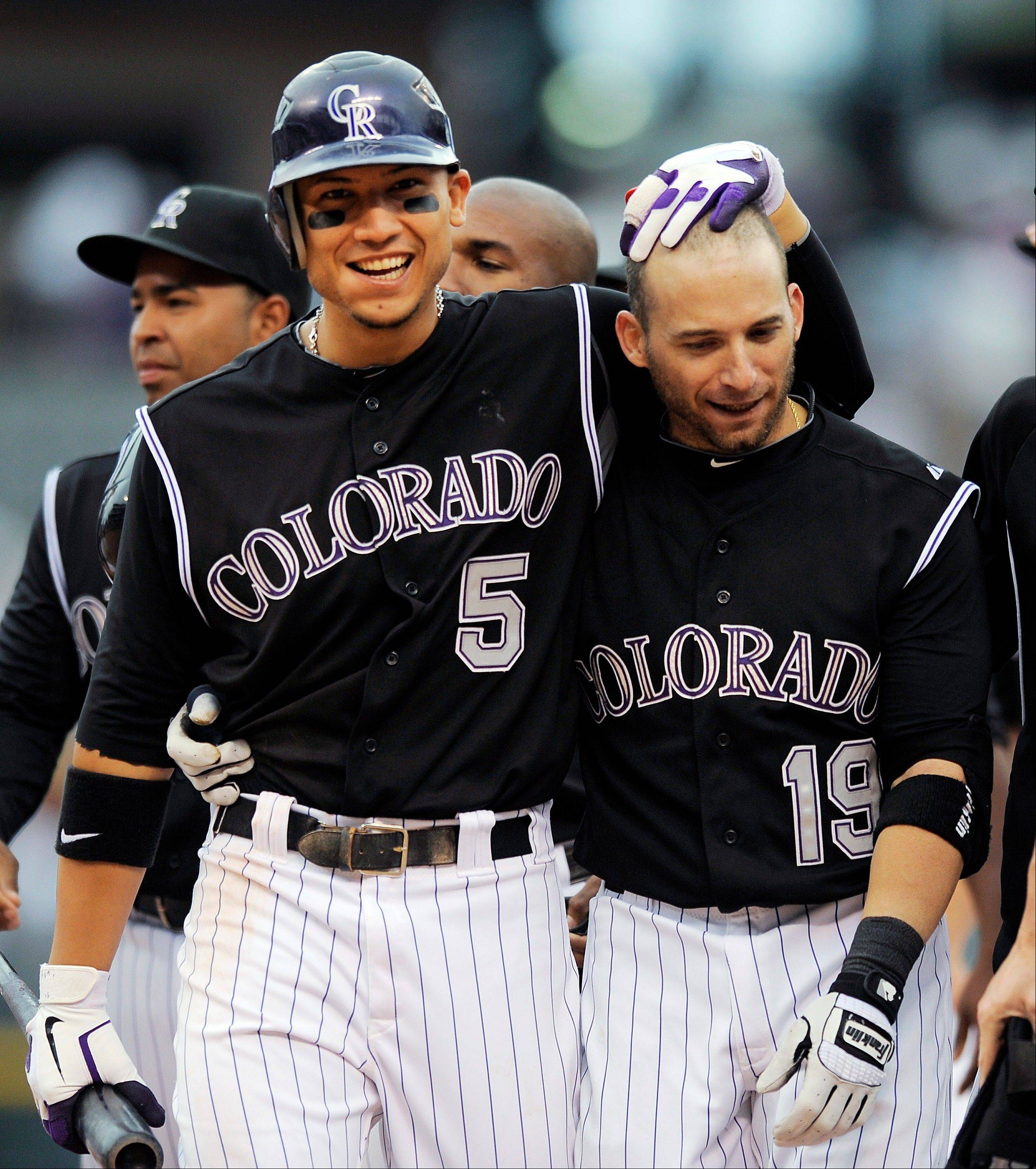 The Rockies' Carlos Gonzalez, left, congratulates Marco Scutaro after Scutaro's game-winning hit in the 11th inning Thursday against the Nationals.