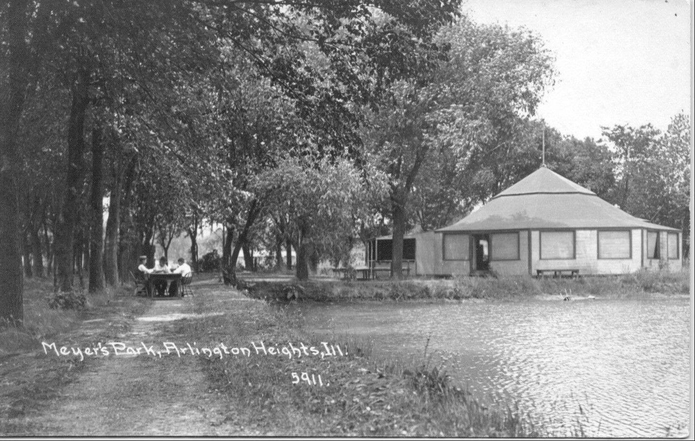 Meyer's Park and pond, with a few picnickers. Once a hot spot for activity, the park is now the site of the village hall.