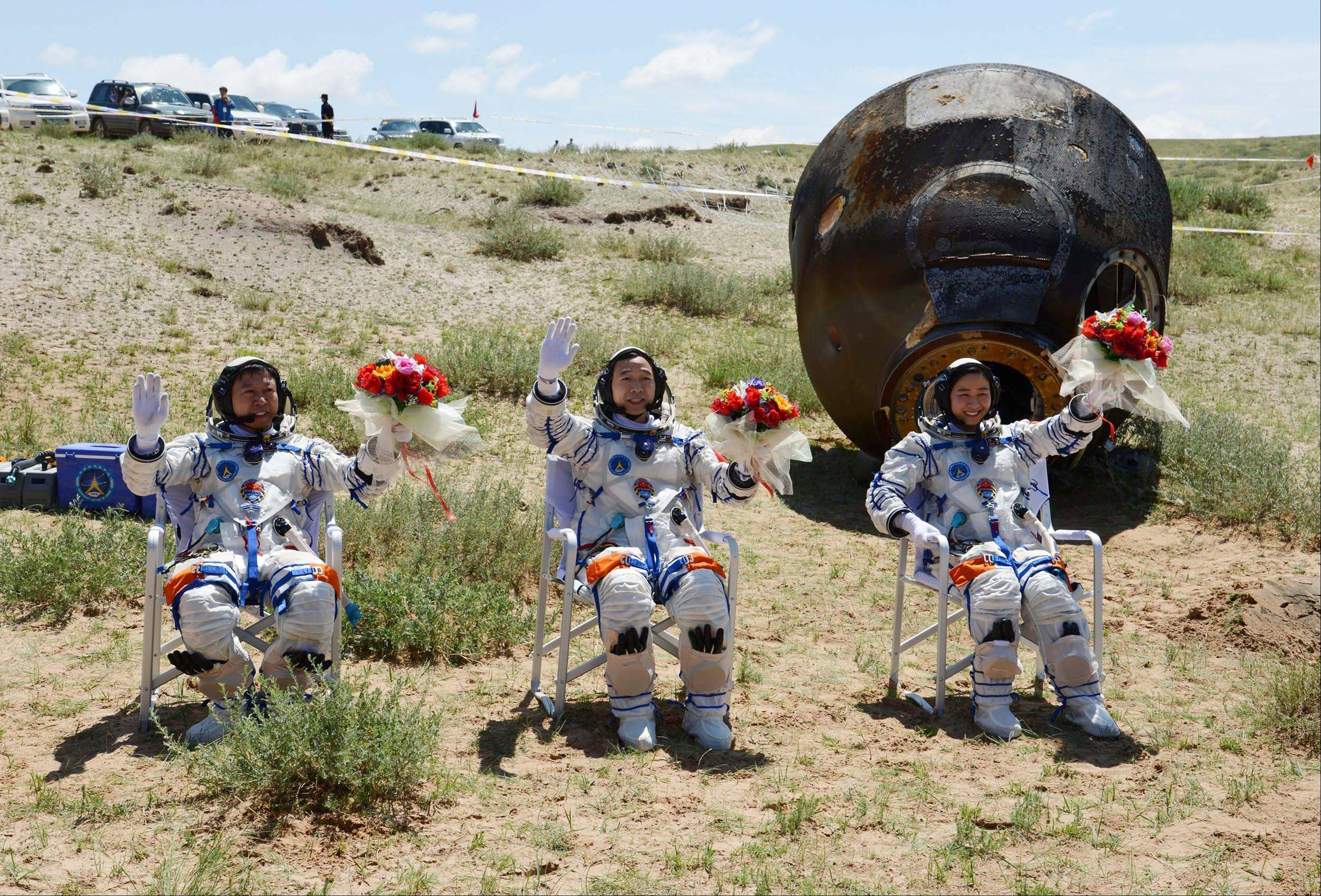 Chinese astronauts, from left, Liu Wang, Jing Haipeng and Liu Yang, wave with flowers after the re-entry capsule of China's Shenzhou 9 spacecraft, back, landed in Siziwang Banner of northern China's Inner Mongolia region.