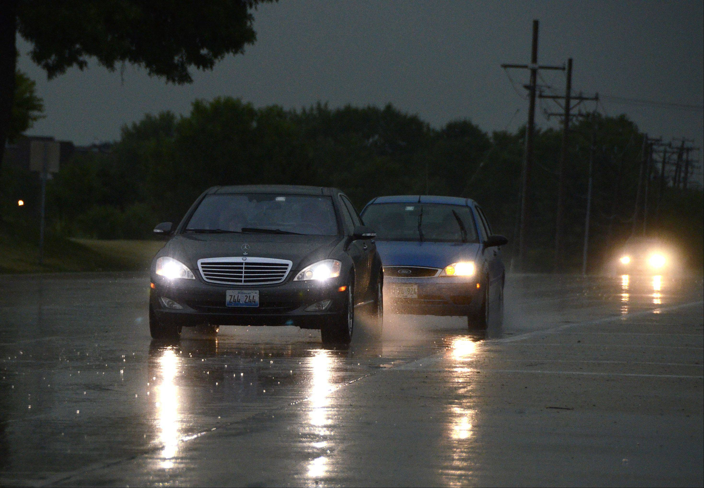 Day turns to night as rain finally comes to the area Friday morning as motorists make their way down Algonquin Road near Harper College.