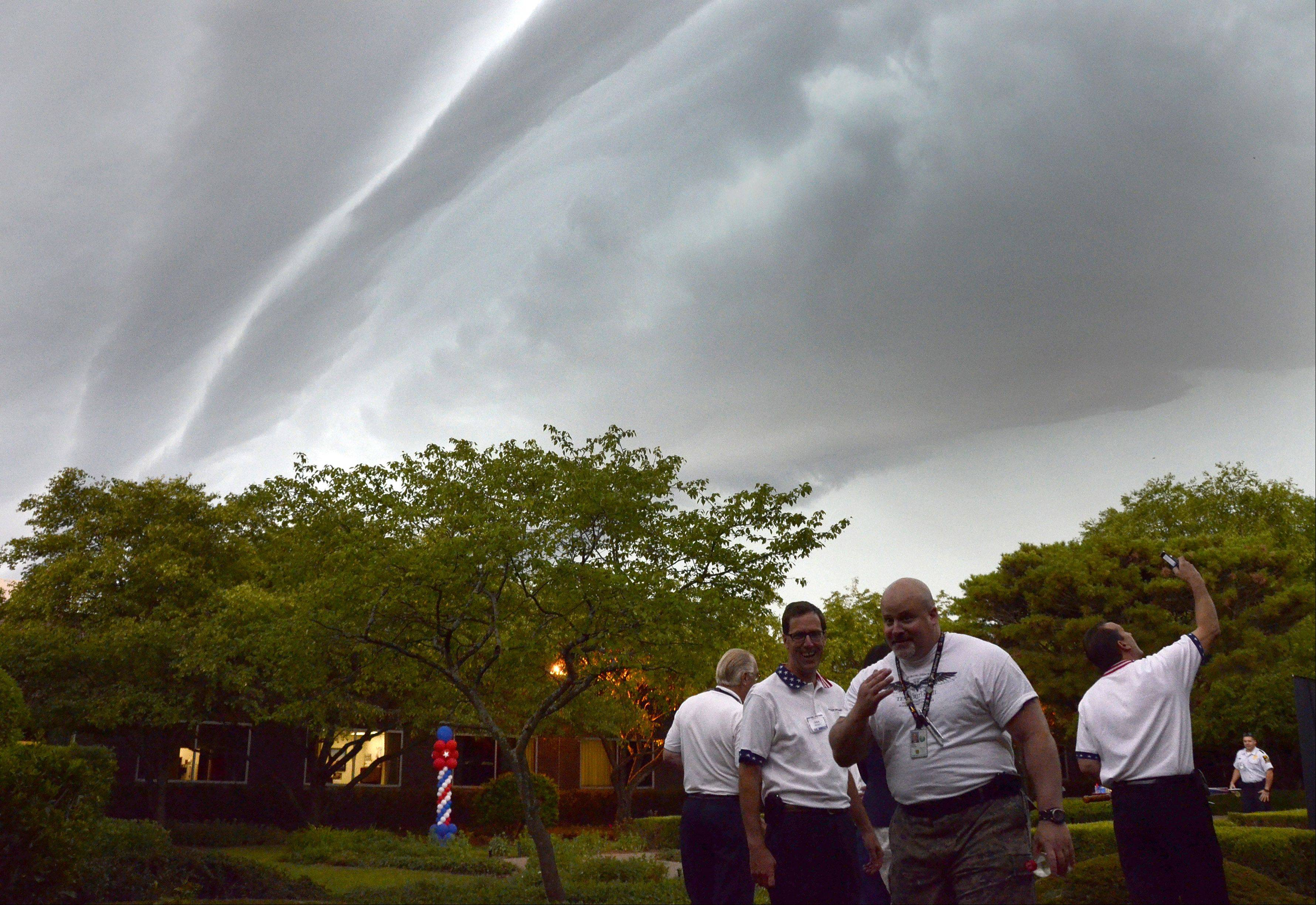 Northrop Grumman employees decide to head inside and the delay the opening of America Day as a storm front rolls in Friday morning in Rolling Meadows.