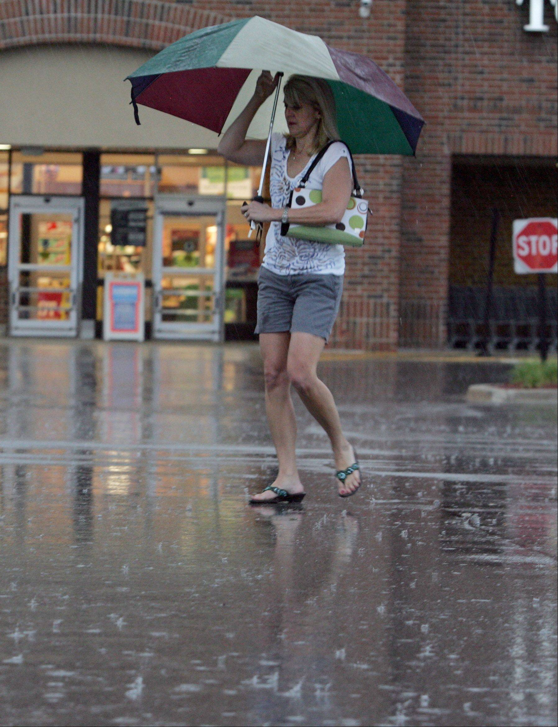 Lisa Balon of Wheaton needed an umbrella as she did her grocery shopping in Wheaton on Friday after storms and much needed rain moved into the Chicago area.