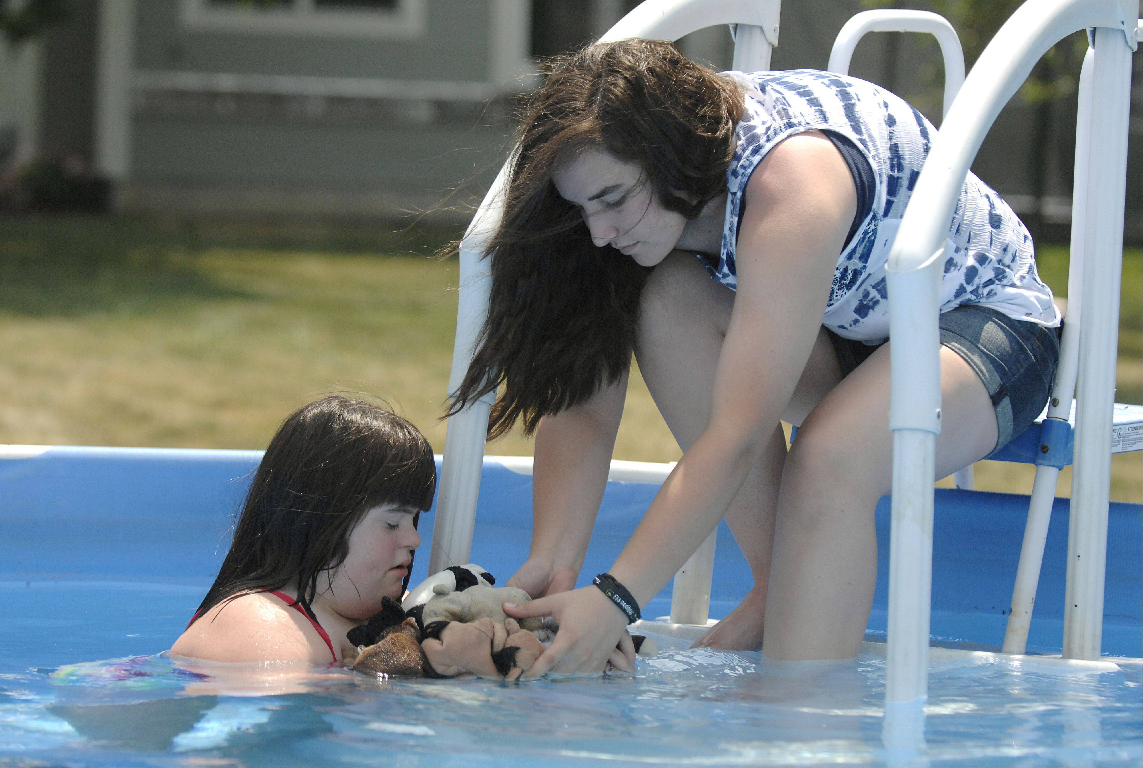 Kara Peters, 13, is handed her stuffed animals by sister, Marisa, 15, while spending time Thursday in their pool. Kara will be receiving a multipurpose service dog next spring with the help of the Elburn Lions and Leo clubs.