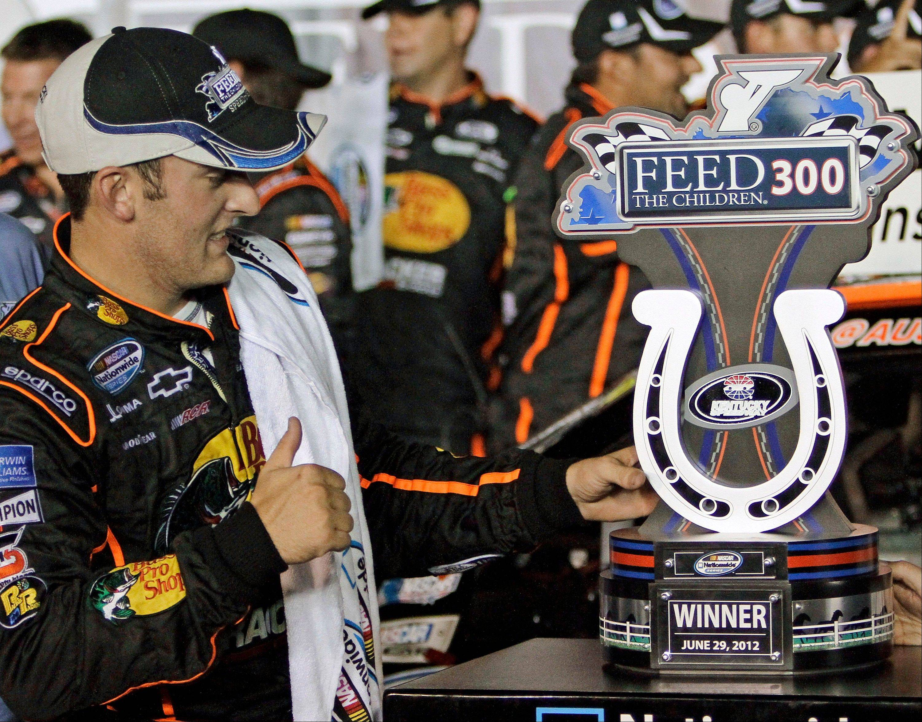 Austin Dillon gives a thumbs-up to the trophy after capturing the NASCAR Nationwide Series auto race Friday night at Kentucky Speedway in Sparta, Ky.