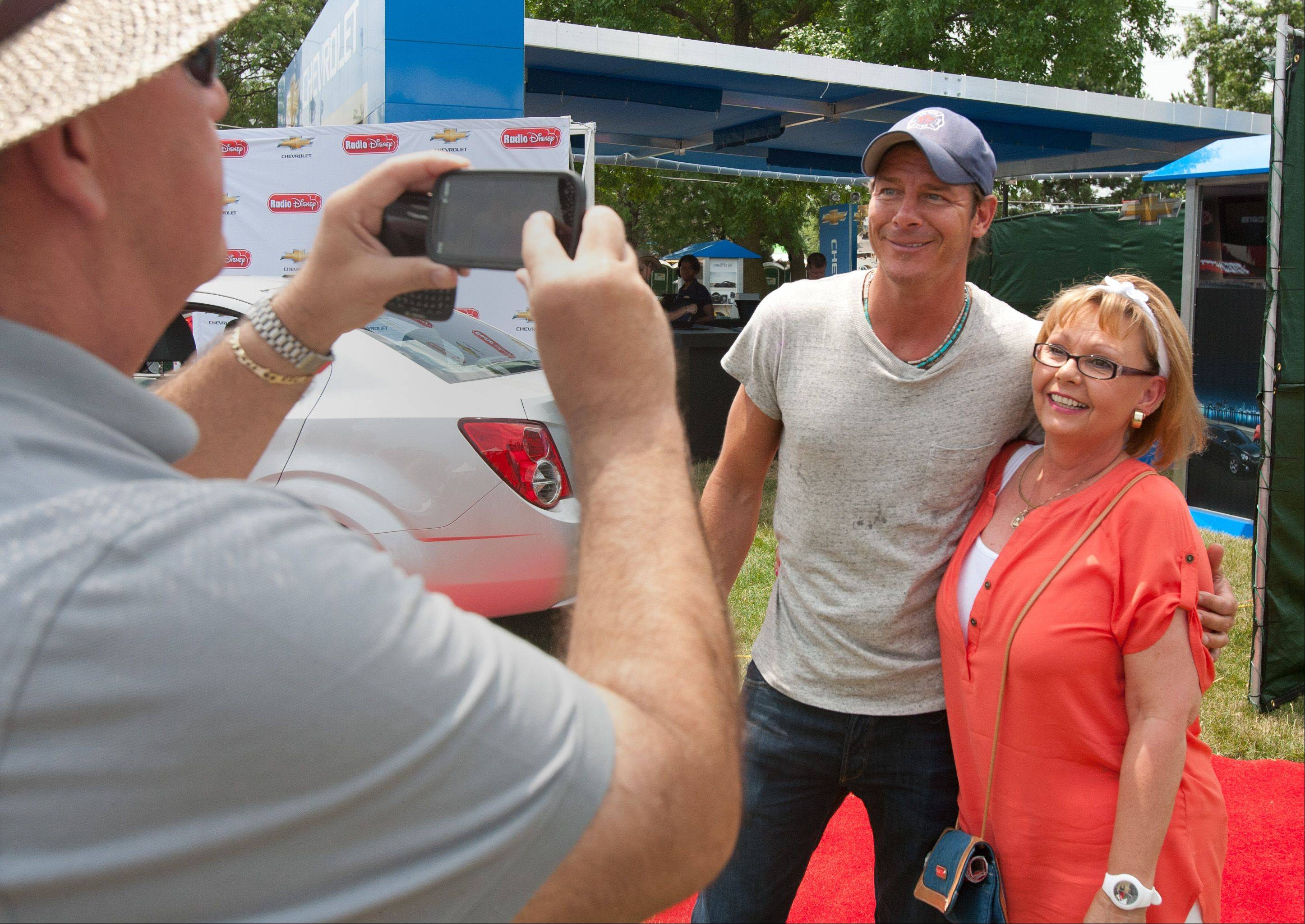 """Extreme Makeover: Home Edition"" star Ty Pennington poses for a photo with Debbie Burke of Downers Grove as he moves around Naperville's Ribfest as part of the Sears Grilling is Happiness team."