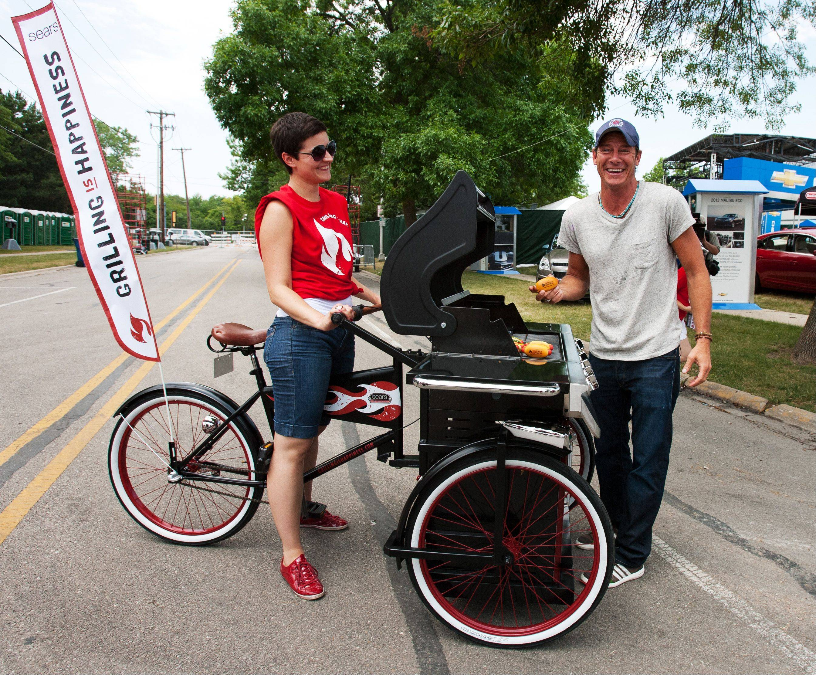 """Extreme Makeover: Home Edition"" star Ty Pennington offers grilling advice Saturday at Naperville's Ribfest. Reka Juhasz, left, steers the mobile grilling unit brought to the festival by the Sears Grilling is Happiness team."