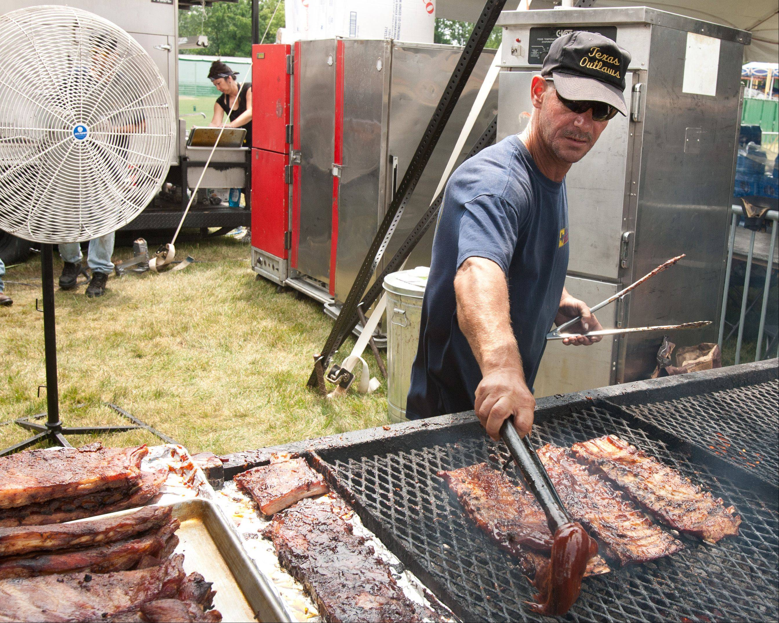 Ron Godsey of Elizabethtown, Kentucky puts the finishing touches on a rack of ribs Saturday at Texas Outlaw's booth at Ribfest in Naperville.