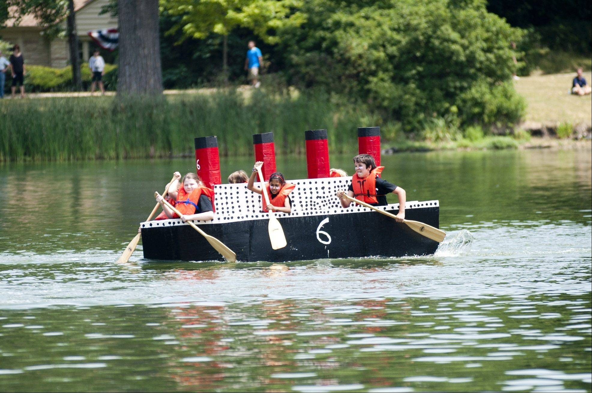 Crew members aboard a cardboard boat built to look like the Titanic compete Saturday in the annual Lake Ellyn Cardboard Regatta in Glen Ellyn.