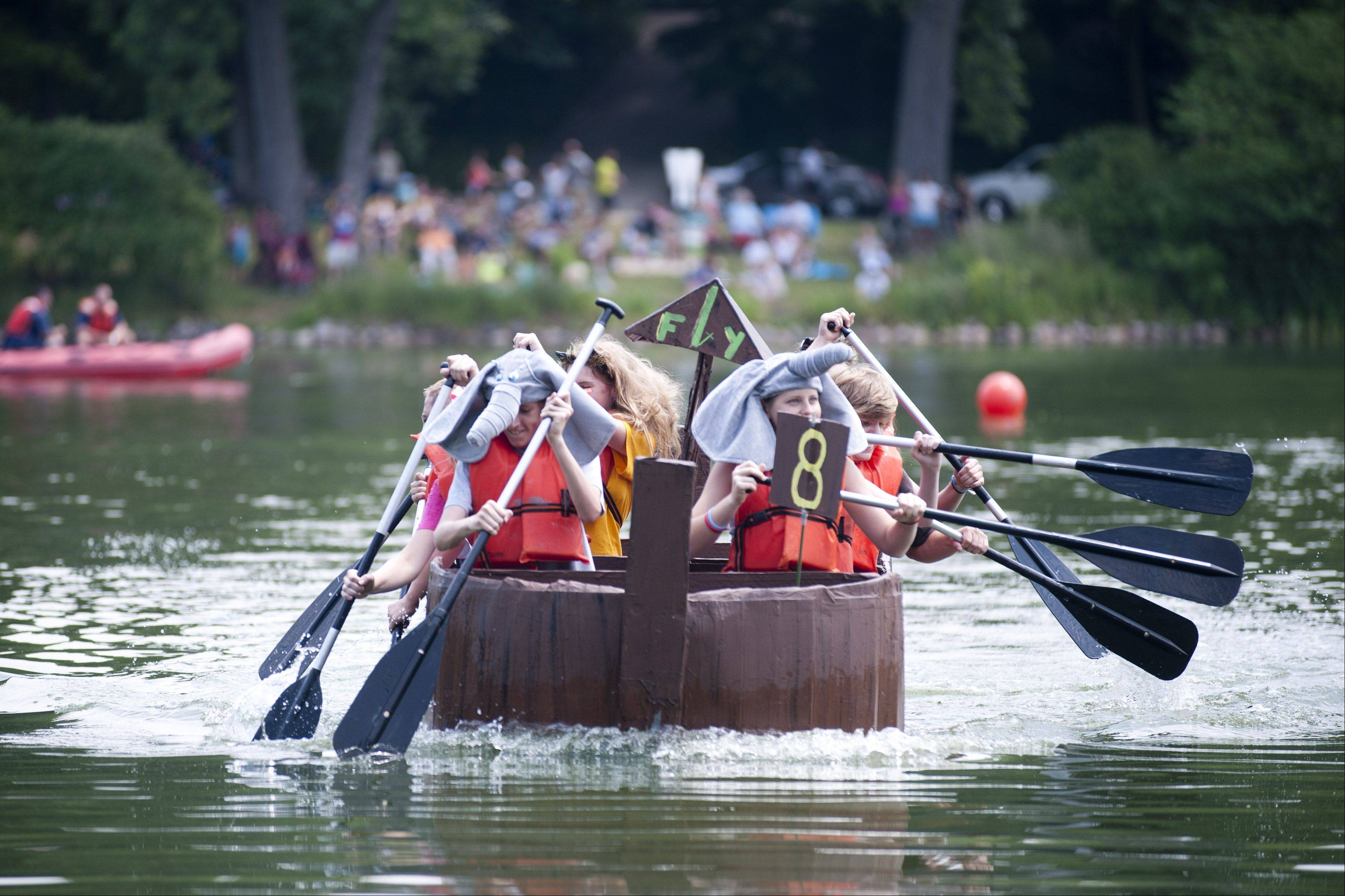 "Team members paddle their boat, called ""Genesis,"" on Saturday during the Lake Ellyn Cardboard Regatta in Glen Ellyn."
